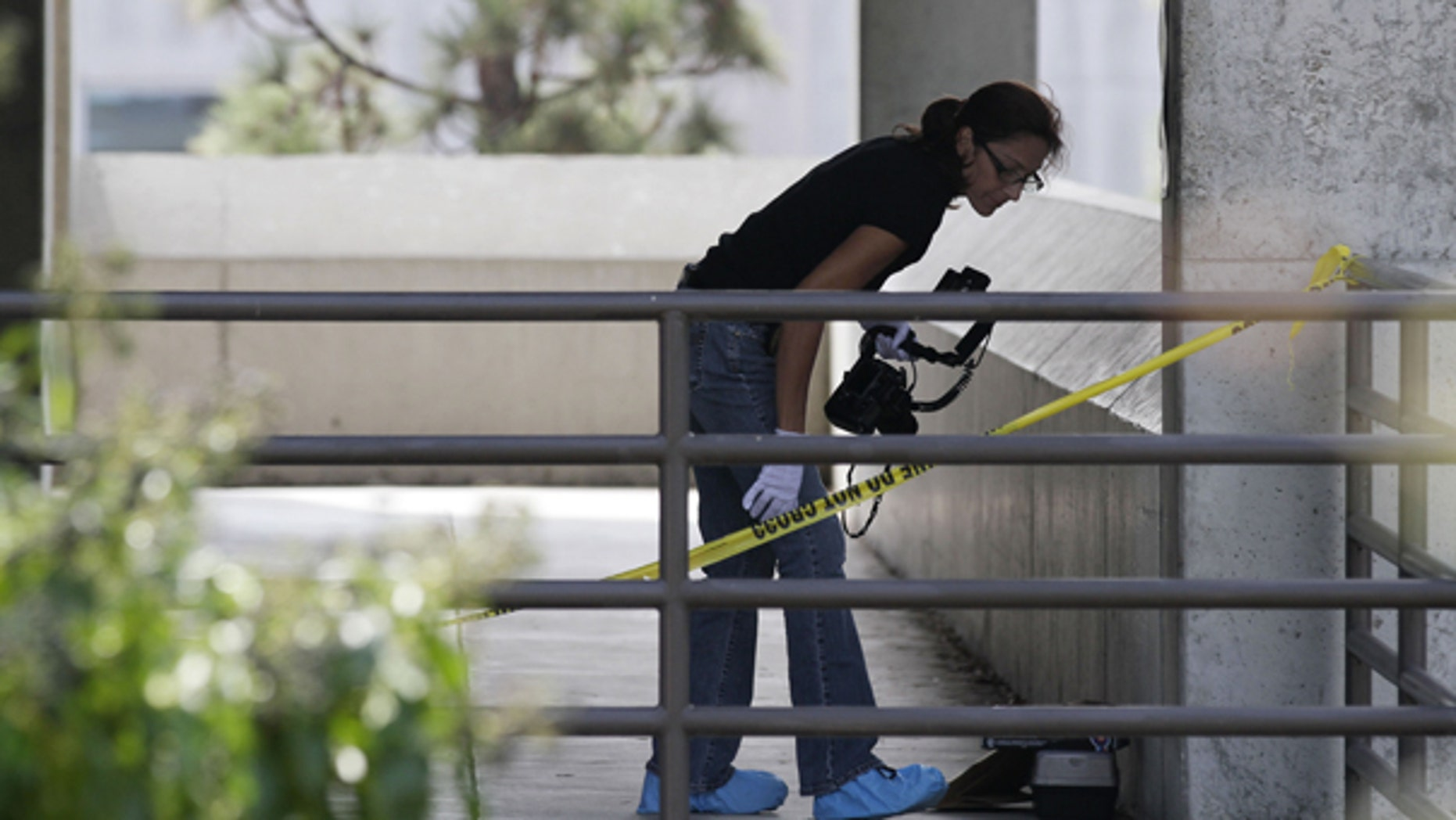 Oct. 13: A police official works at the scene where the body of a woman was found in a bathroom Tuesday night on the campus of San Diego City College.