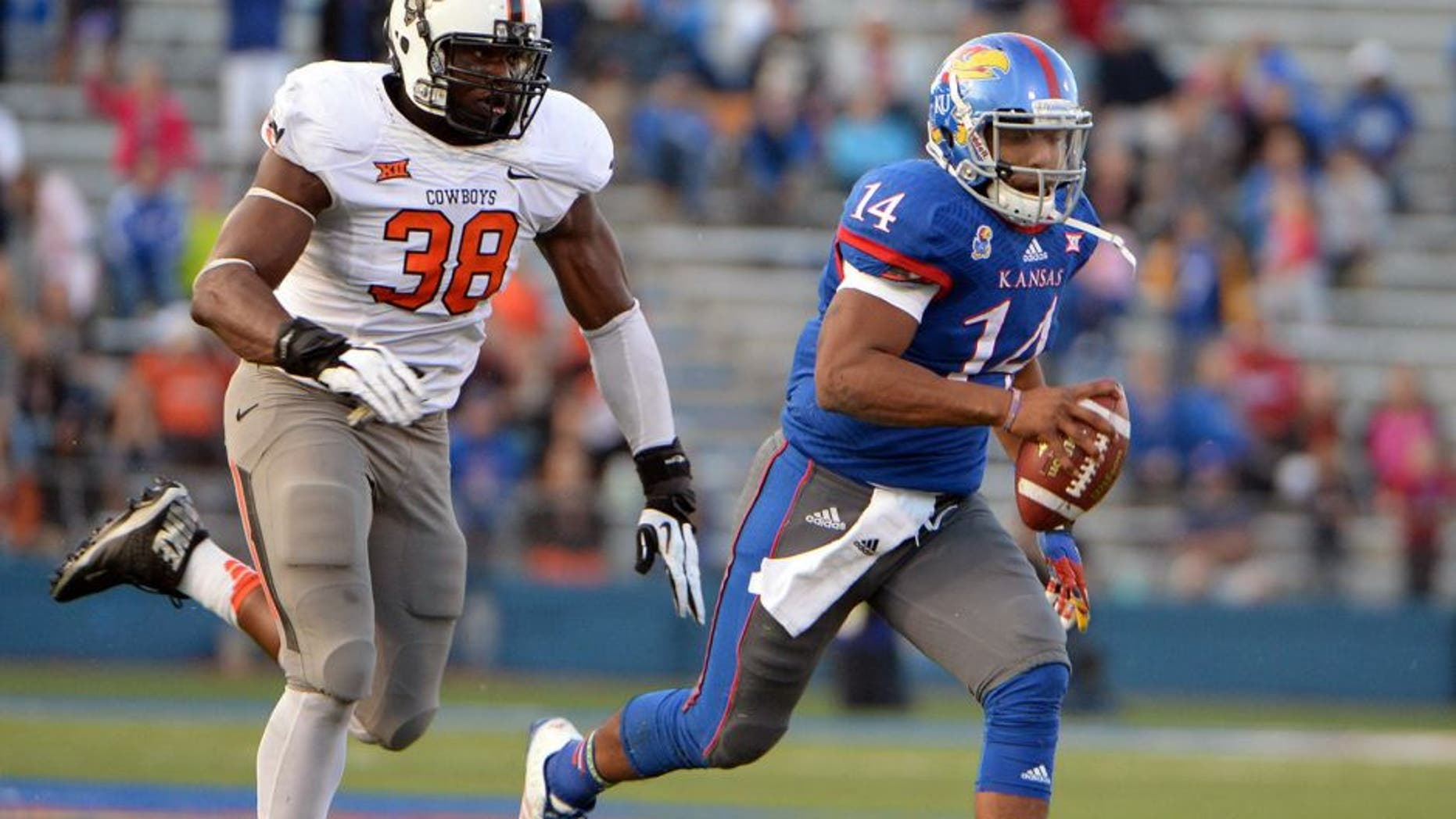 Oct 11, 2014; Lawrence, KS, USA; Kansas Jayhawks quarterback Michael Cummings (14) is chased by Oklahoma State Cowboys defensive end Emmanuel Ogbah (38) in the second half at Memorial Stadium. Oklahoma State won the game 27-20. Mandatory Credit: John Rieger-USA TODAY Sports