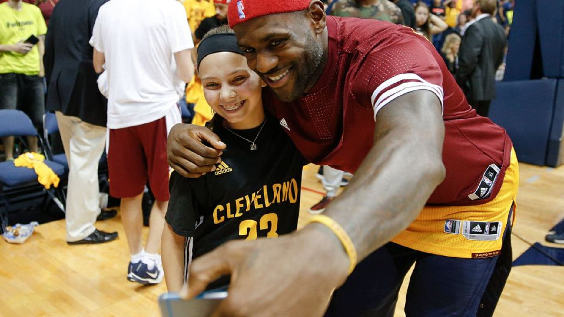 Cleveland Cavaliers forward LeBron James, right, takes a selfie with a young fan after an NBA preseason basketball game against the Atlanta Hawks, Wednesday, Oct. 7, 2015, in Cincinnati. The Hawks won 98-96. (AP Photo/John Minchillo)