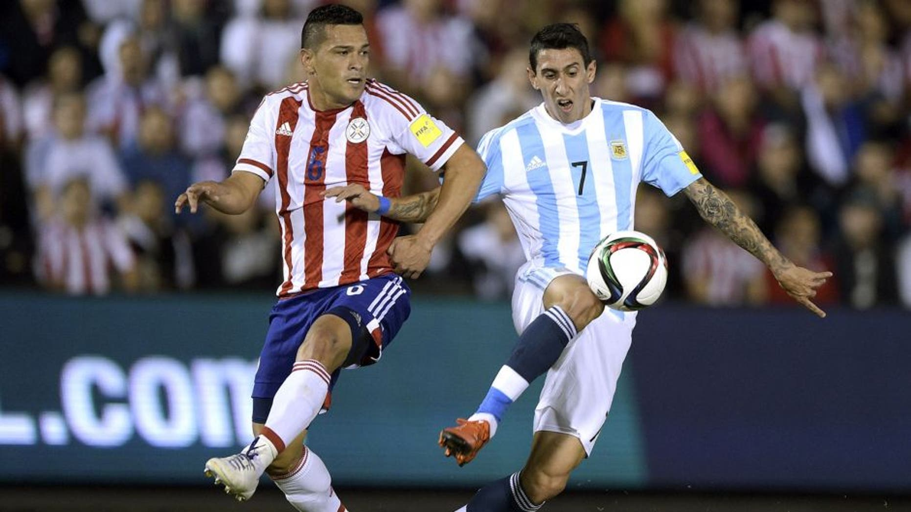 Paraguay's Miguel Angel Samudio (L) and Argentina's forward Angel Di Maria vie for the ball during their Russia 2018 FIFA World Cup South American Qualifiers football match, at the Defensores del Chaco stadium in Asuncion, on October 13, 2015. AFP PHOTO / JUAN MABROMATA (Photo credit should read JUAN MABROMATA/AFP/Getty Images)