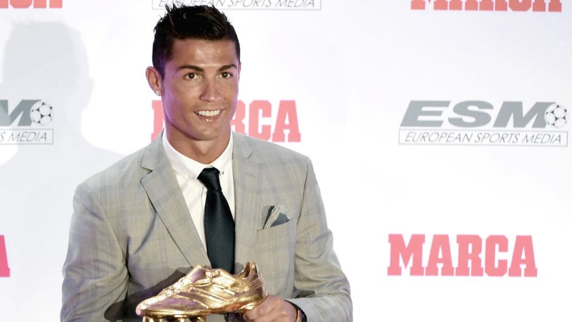 Real Madrid's Portuguese forward Cristiano Ronaldo poses with his fourth European Golden Shoe in Madrid, on October 13, 2015. Cristiano, who ended the season with 48 goals from 35 appearances, won the Golden Shoe in 2008 while he was at Manchester United, in 2011 with Real Madrid and shared it with Luis Suarez last year. AFP PHOTO / JAVIER SORIANO (Photo credit should read JAVIER SORIANO/AFP/Getty Images)