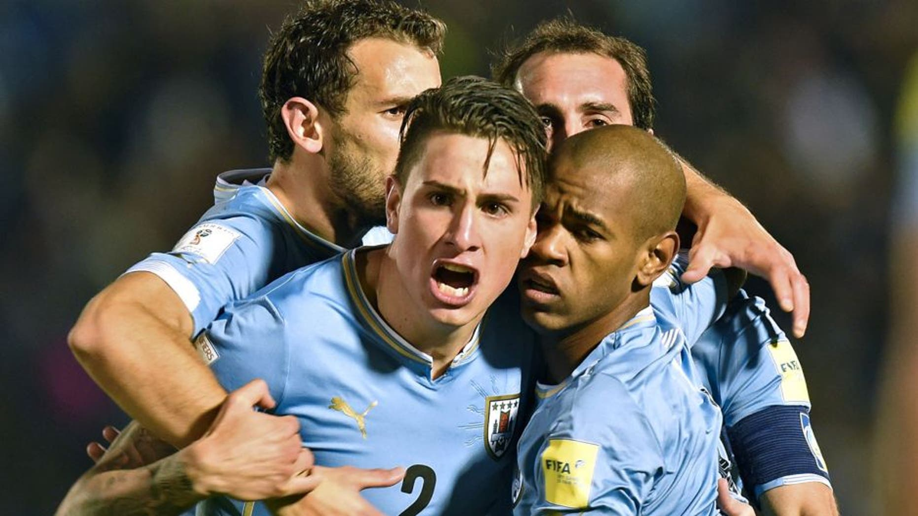 Uruguay's forward Diego Rolan (R, front) celebrates with teammates Jose Maria Gimenez (C), Christian Stuani (L) and Diego Godin after scoring against Colombia during their Russia 2018 FIFA World Cup South American Qualifiers football match, at the Estadio Centenario stadium in Montevideo, on October 13, 2015. AFP PHOTO / PABLO PORCIUNCULA (Photo credit should read PABLO PORCIUNCULA/AFP/Getty Images)