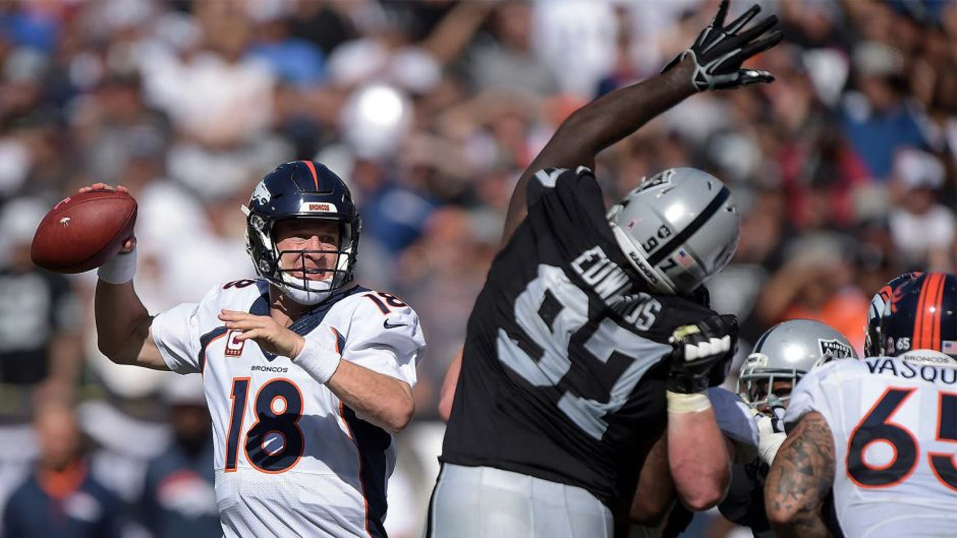 Oct 11, 2015; Oakland, CA, USA; Denver Broncos quarterback Peyton Manning (18) throws a pass under pressure by Oakland Raiders defensive end Mario Edwards Jr. (97) at O.co Coliseum. Mandatory Credit: Kirby Lee-USA TODAY Sports