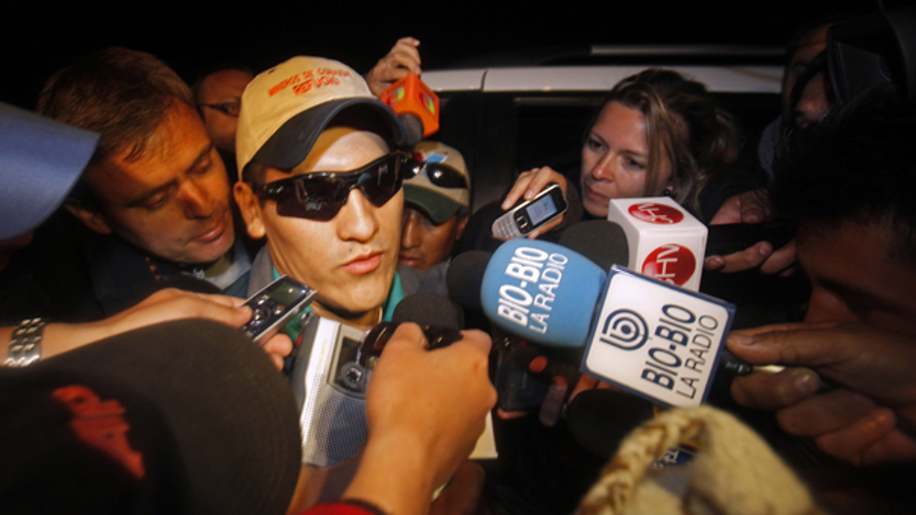 Oct. 14: Rescued miner Carlos Mamani, from Bolivia, is surrounded by the press as he arrives at his home in Copiapo, Chile.