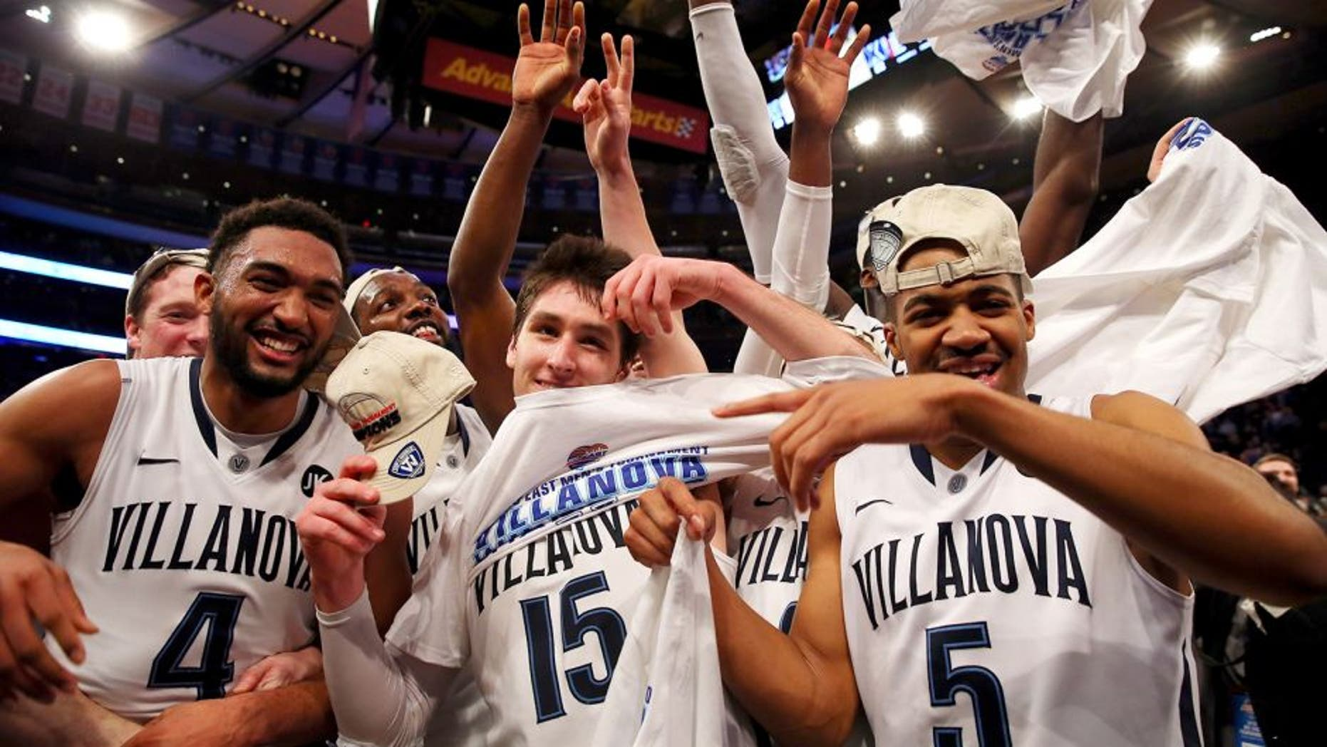 NEW YORK, NY - MARCH 14: Darrun Hilliard #4, Ryan Arcidiacono #15, and Phil Booth #5 of the Villanova Wildcats celebrate on the court after defeating the Xavier Musketeers 69-52 in the championship game of the Big East basketball tournament at Madison Square Garden on March 14, 2015 in New York City. (Photo by Elsa/Getty Images)