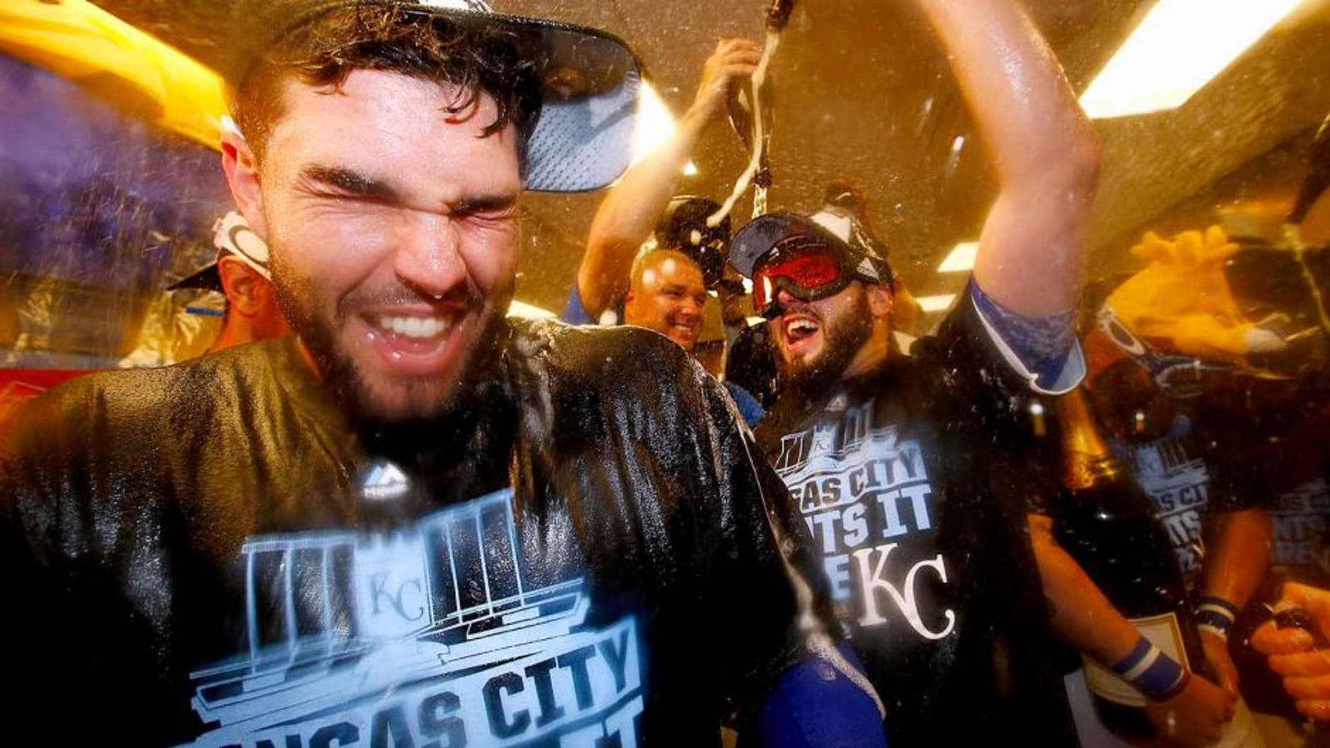 KANSAS CITY, MO - OCTOBER 14: Eric Hosmer #35 of the Kansas City Royals, left, celebrates with teammates in the clubhouse after defeating the Houston Astros 7-2 in game five of the American League Divison Series at Kauffman Stadium on October 14, 2015 in Kansas City, Missouri. (Photo by Jamie Squire/Getty Images)