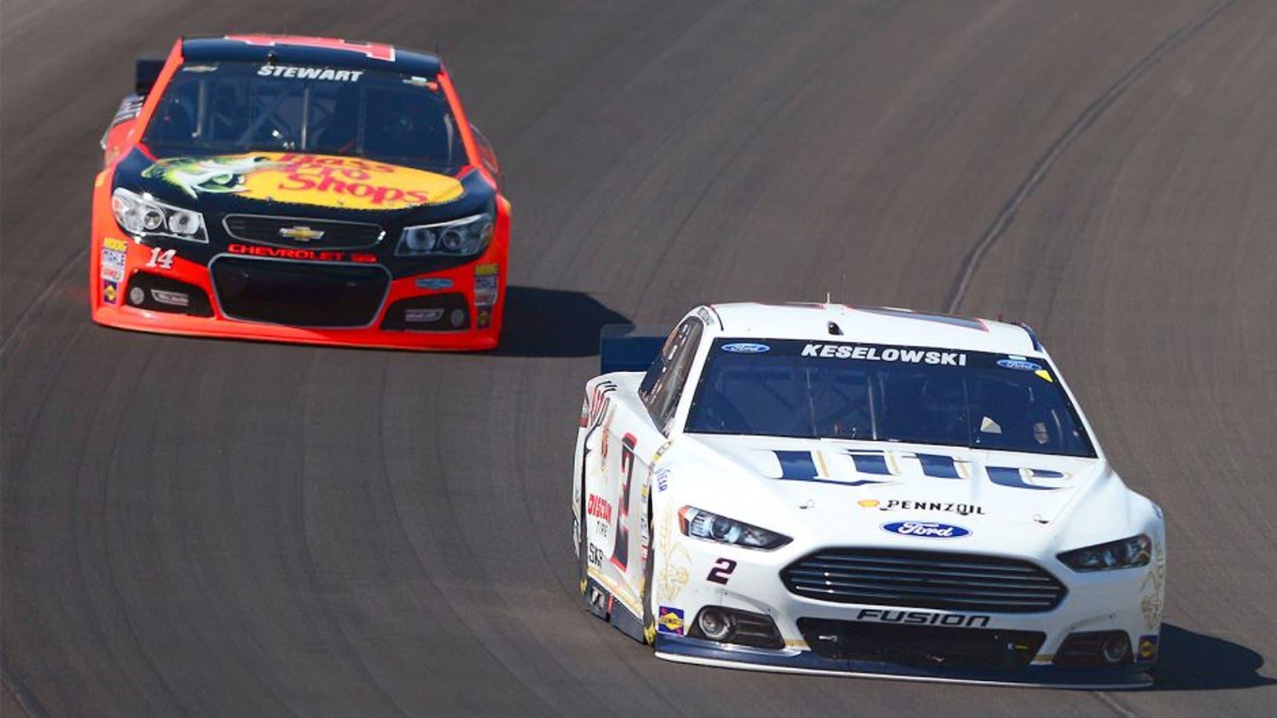 Jun 15, 2014; Brooklyn, MI, USA; NASCAR Sprint Cup Series driver Brad Keselowski leads Tony Stewart during the Quicken Loans 400 at Michigan International Speedway. Mandatory Credit: Andrew Weber-USA TODAY Sports