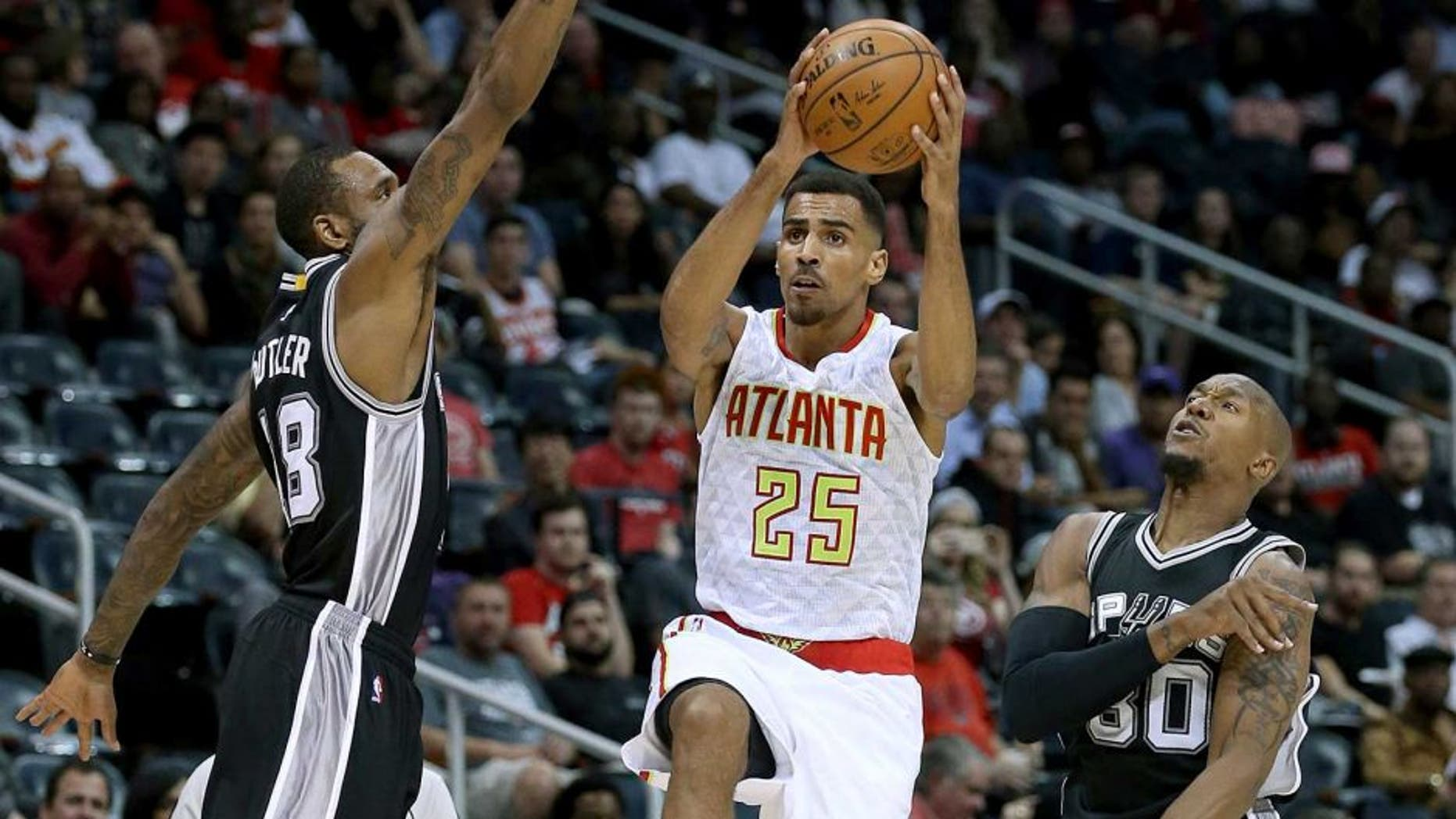 Oct 14, 2015; Atlanta, GA, USA; Atlanta Hawks guard Thabo Sefolosha (25) attempts a shot against San Antonio Spurs forward Rasual Butler (18, left) and forward David West (30) in the first quarter of their game at Philips Arena. Mandatory Credit: Jason Getz-USA TODAY Sports