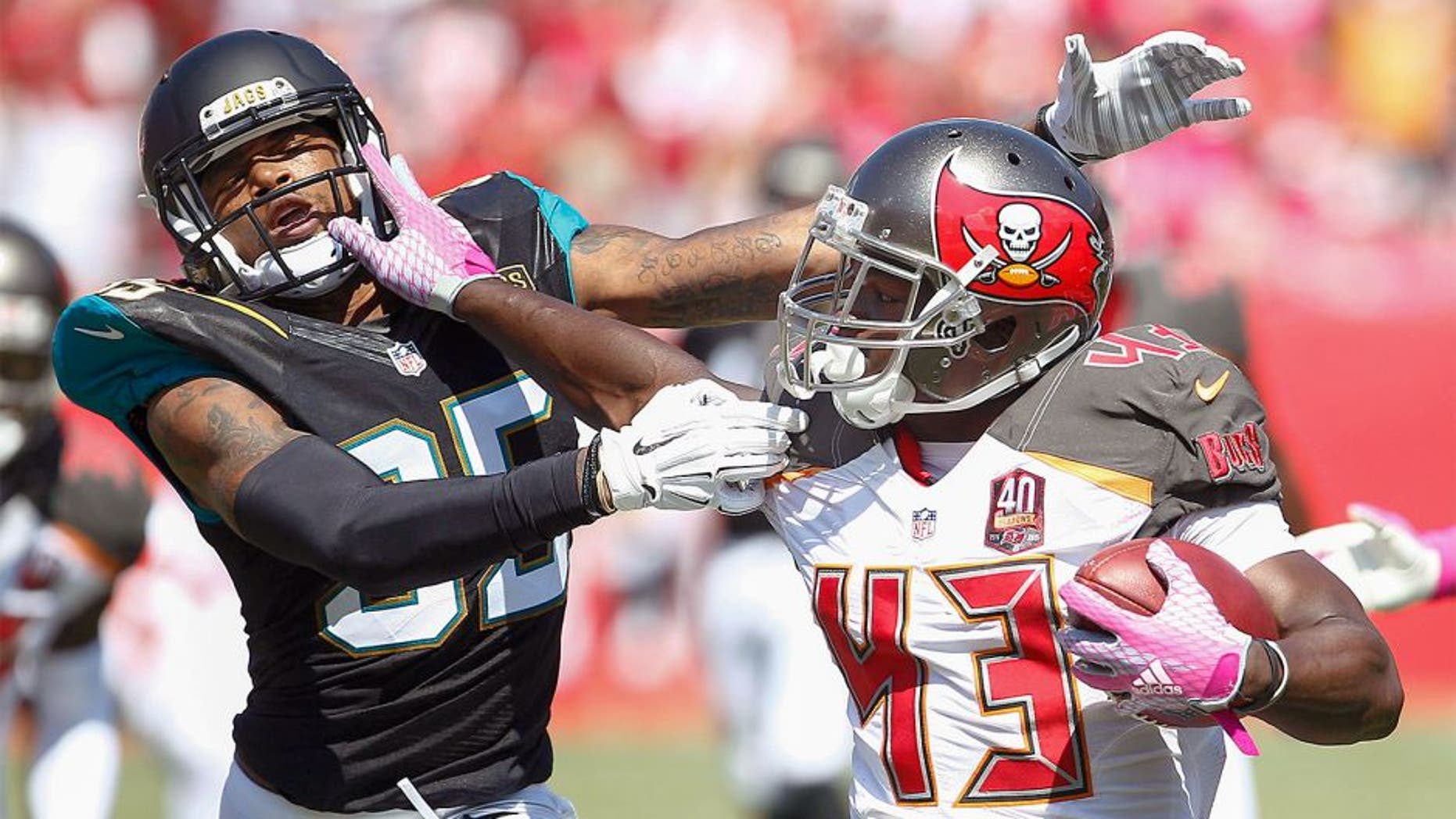 Oct 11, 2015; Tampa, FL, USA; Jacksonville Jaguars cornerback Demetrius McCray (35)is stiff armed by Tampa Bay Buccaneers running back Bobby Rainey (43) during the second quarter of an NFL football game at Raymond James Stadium. Mandatory Credit: Reinhold Matay-USA TODAY Sports