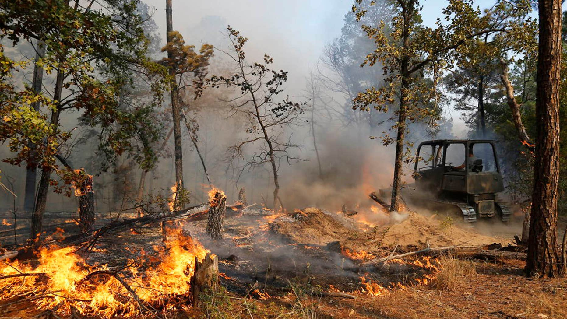 Oct. 14, 2015: Firefighters work with heavy machinery to contain the fire near Smithville, Texas.