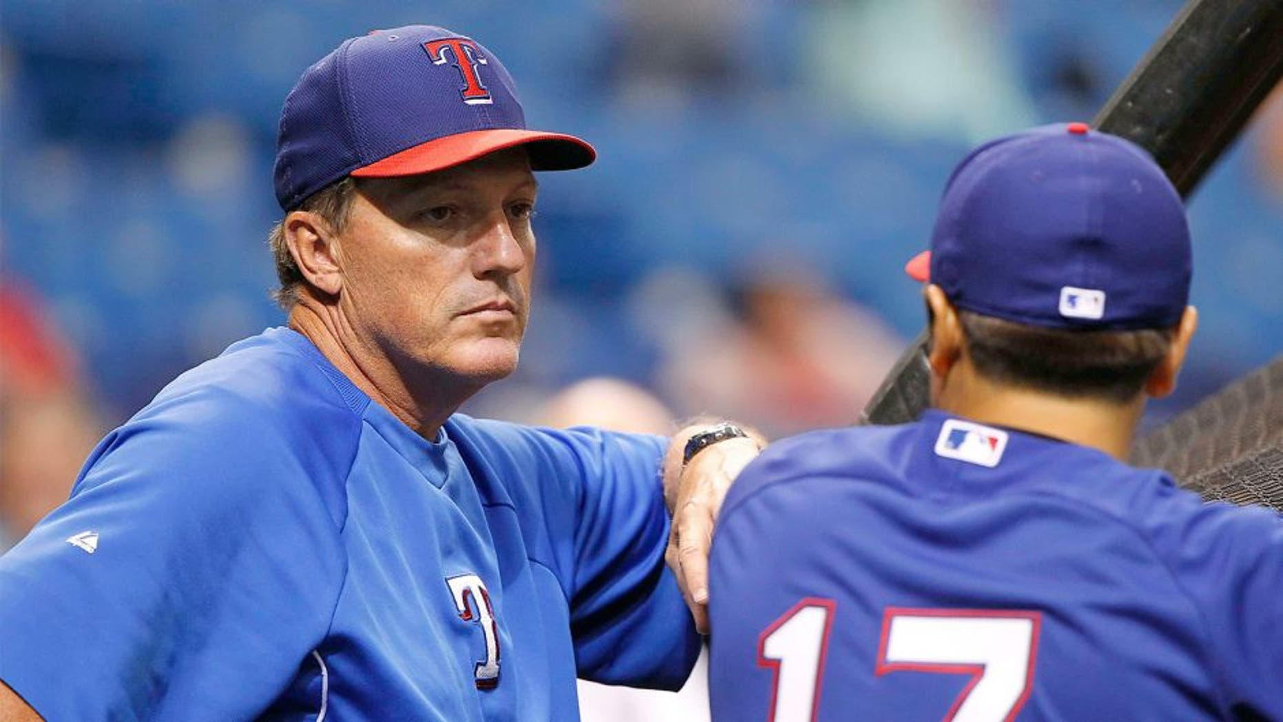 Apr 4, 2014; St. Petersburg, FL, USA; Texas Rangers batting coach Dave Magadan (14) talks with left fielder Shin-Soo Choo (17) prior to the game against the Tampa Bay Rays at Tropicana Field. Mandatory Credit: Kim Klement-USA TODAY Sports