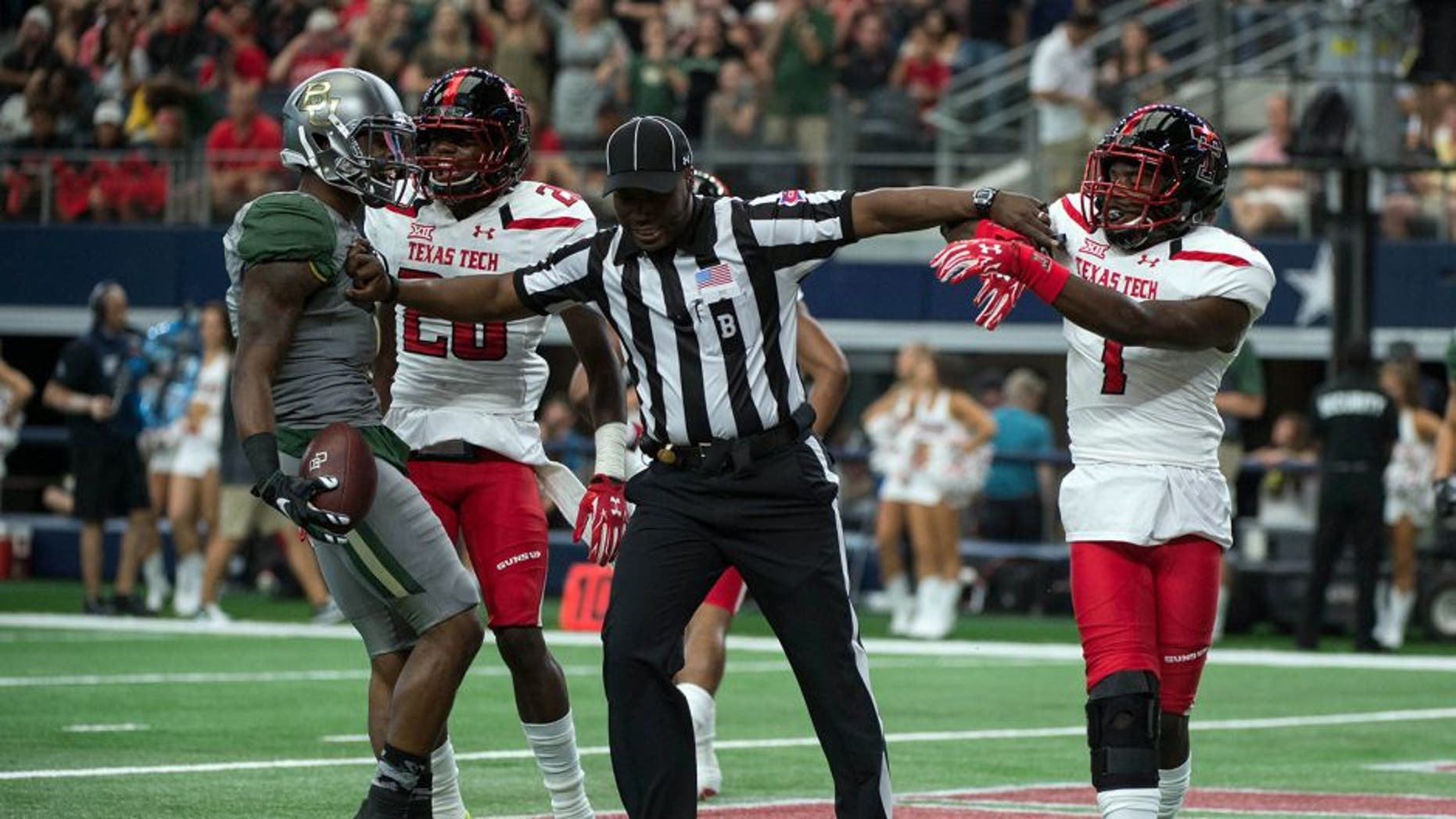 Oct 3, 2015; Arlington, TX, USA; Baylor Bears wide receiver Corey Coleman (1) and Texas Tech Red Raiders defensive back Jah'Shawn Johnson (7) are separated by back judge Lyndon Nixon after Coleman scores a touchdown during the first quarter at AT&T Stadium. Mandatory Credit: Jerome Miron-USA TODAY Sports