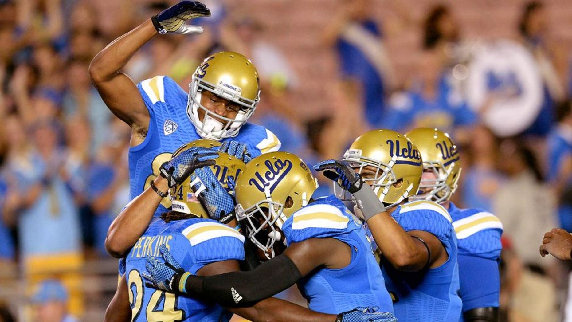 Sep 6, 2014; Pasadena, CA, USA; UCLA Bruins celebrate with running back Paul Perkins (24) after scoring a touchdown in the first quarter of the game against the Memphis Tigers at the Rose Bowl. Mandatory Credit: Jayne Kamin-Oncea-USA TODAY Sports