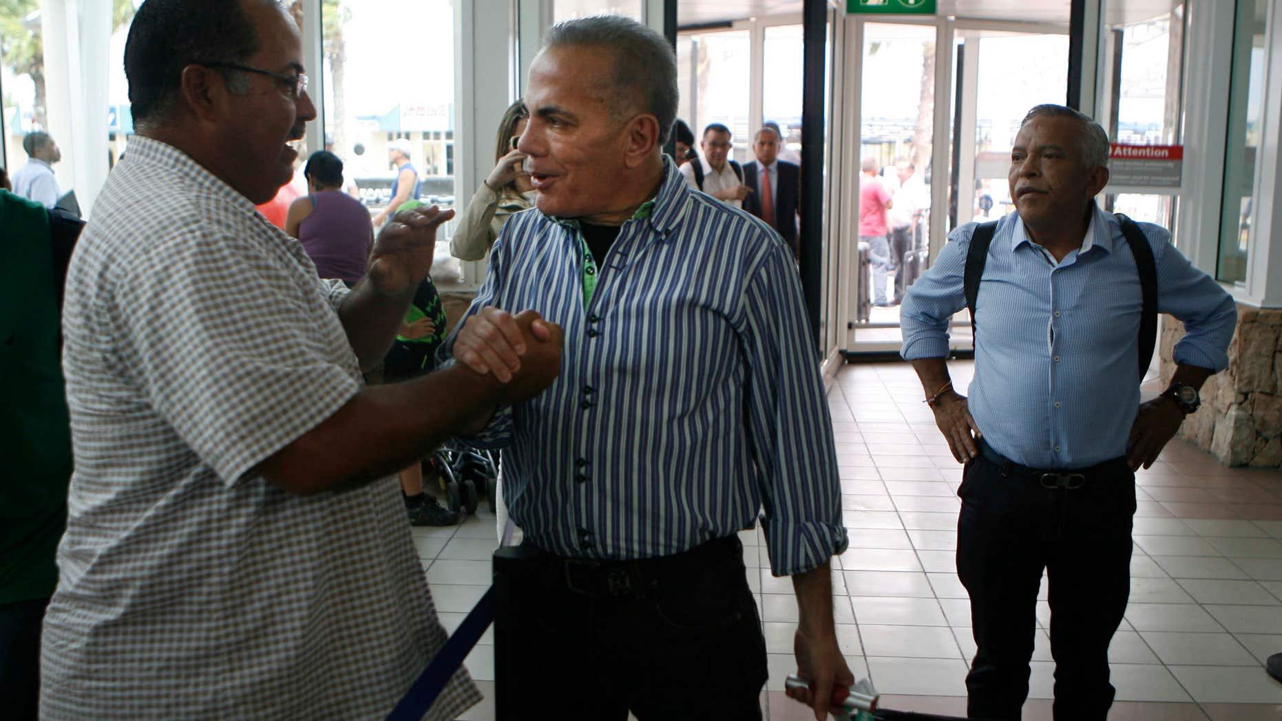 Oct. 15, 2015: A unidentified man shake hands with Venezuelan opposition leader Manuel Rosales, center, before he flies to Venezuela, at the airport near Oranjestad, Aruba.