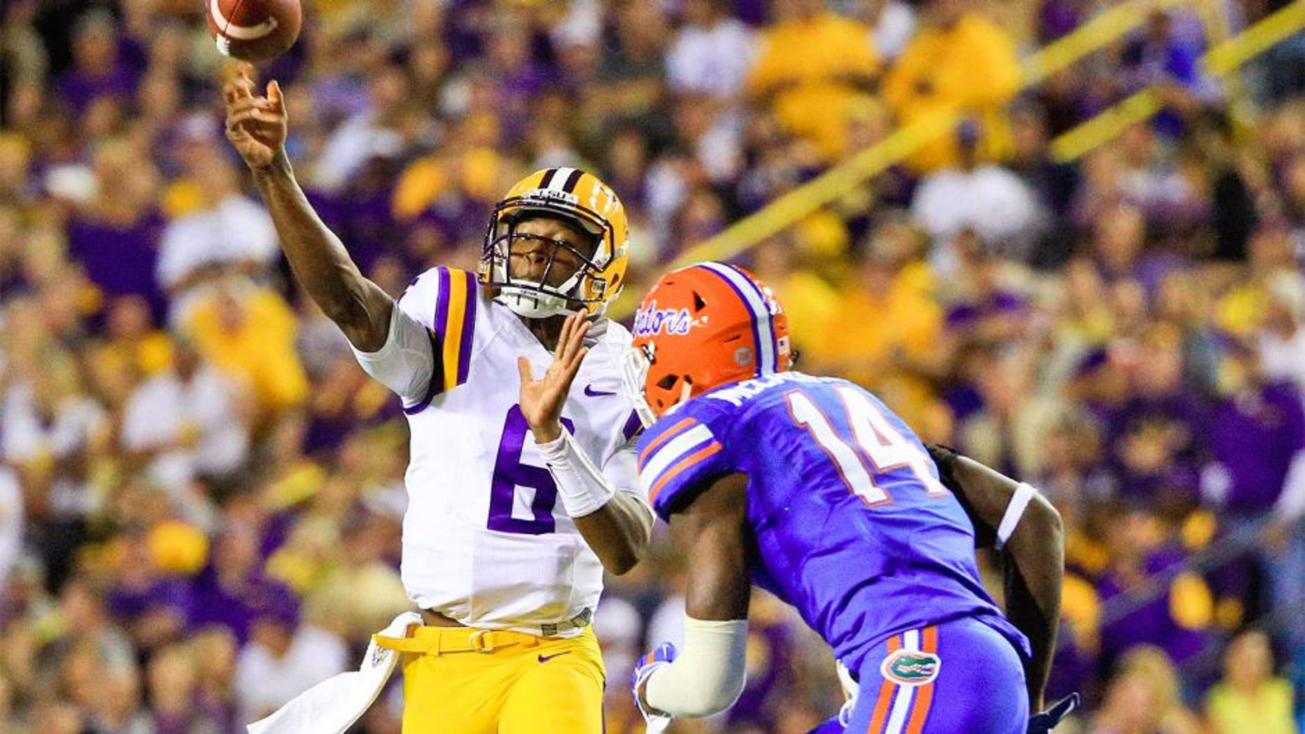 Oct 17, 2015; Baton Rouge, LA, USA; LSU Tigers quarterback Brandon Harris (6) throws as Florida Gators defensive lineman Alex McCalister (14) defends during the second quarter of a game at Tiger Stadium. Mandatory Credit: Derick E. Hingle-USA TODAY Sports