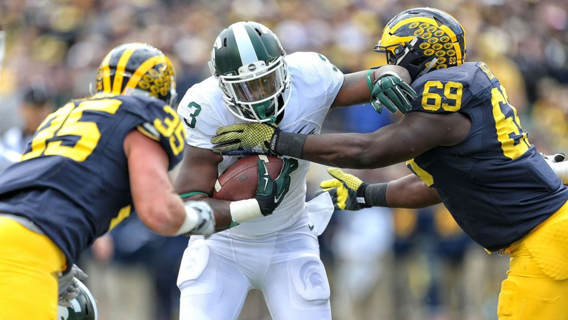Oct 17, 2015; Ann Arbor, MI, USA; Michigan State Spartans running back LJ Scott (3) carries the ball between Michigan Wolverines linebacker Joe Bolden (35) and Michigan Wolverines defensive tackle Willie Henry (69) during the 1st quarter of a game at Michigan Stadium. Mandatory Credit: Mike Carter-USA TODAY Sports