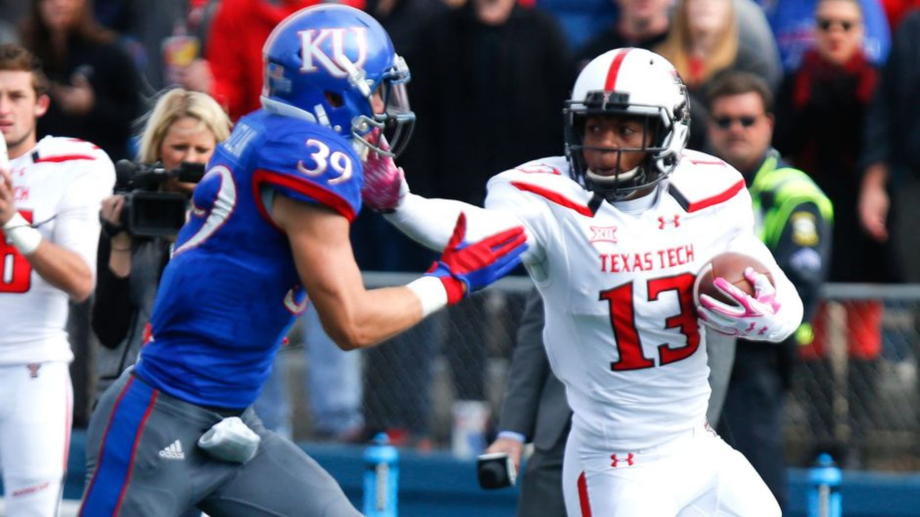 LAWRENCE, KS - OCTOBER 17: Cameron Batson #13 of the Texas Tech Red Raiders fends off Michael Glatczak #39 of the Kansas Jayhawks during the game on October 17, 2015 at Memorial Stadium in Lawrence, Kansas. (Photo by Kyle Rivas/Getty Images)