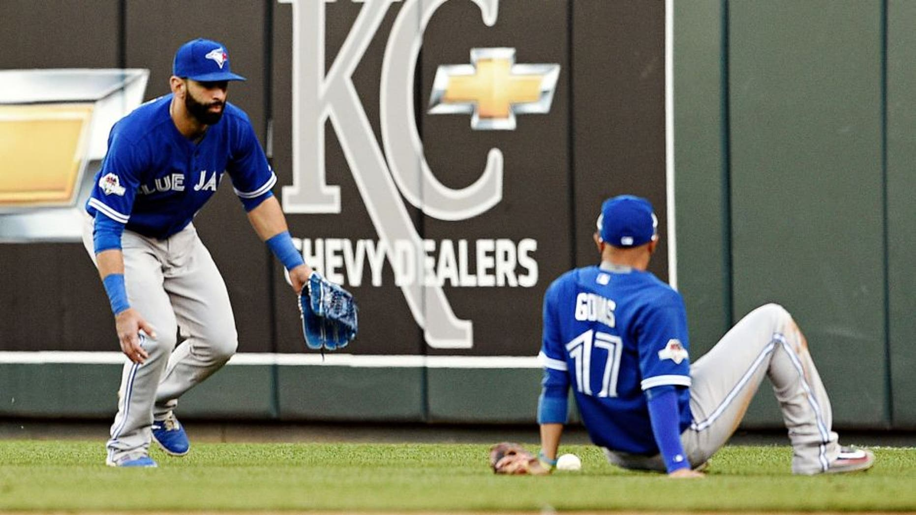 Toronto Blue Jays second baseman Ryan Goins sits on the ground and looks at the fly ball tha fell between himself and right fielder Jose Bautista, left, on a ball hit by the Kansas City Royals' Ben Zobrist in the seventh inning during Game 2 of the ALCS on at Kauffman Stadium in Kansas City, Mo., on Saturday, Oct. 17, 2015. (Shane Keyser/Kansas City Star/TNS via Getty Images)