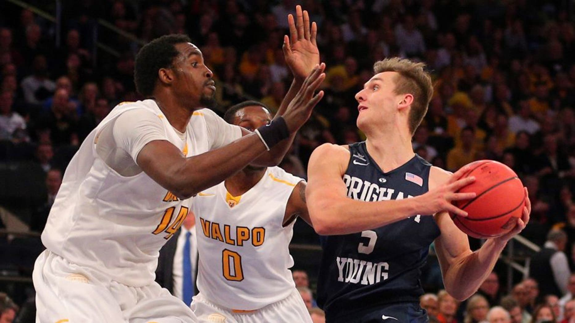 Mar 29, 2016; New York, NY, USA; BYU Cougars guard Kyle Collinsworth (5) prepares to shoot the ball as Valparaiso Crusaders center Vashil Fernandez (14) and guard Keith Carter (0) defend during the second half of a semifinal game of the 2016 NIT basketball tournament at Madison Square Garden. The Crusaders won 72-70. Mandatory Credit: Brad Penner-USA TODAY Sports