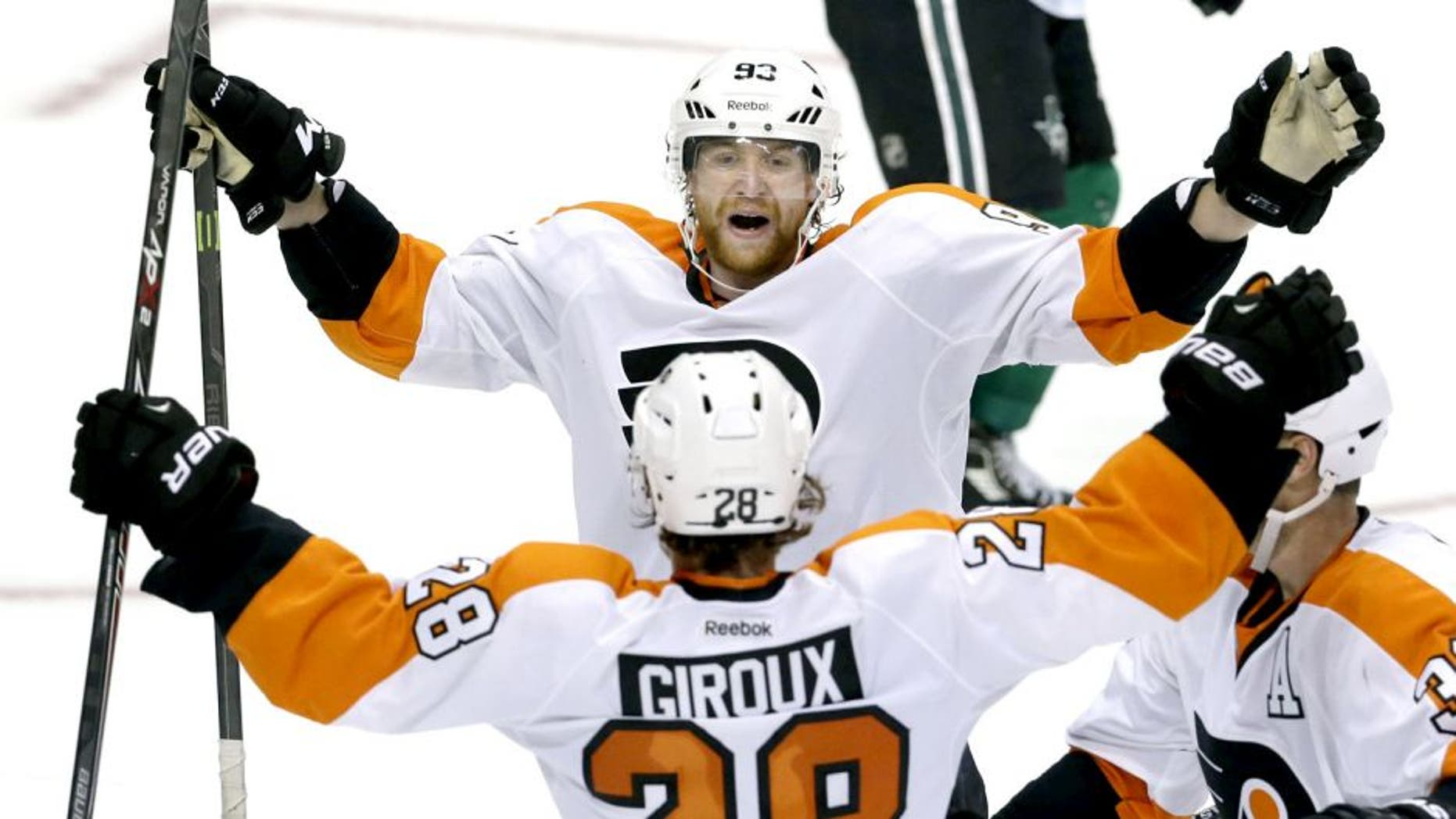 Philadelphia Flyers right wing Jakub Voracek (93) celebrates the game winning goal with teammates center Claude Giroux (28) and defenseman Mark Streit (32) during overtime of an NHL hockey game against the Dallas Stars Saturday, Oct. 18, 2014, in Dallas. The Flyers won 6-5. (AP Photo/LM Otero)