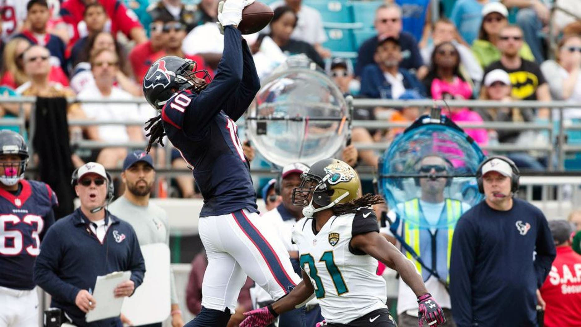 Oct 18, 2015; Jacksonville, FL, USA; Houston Texans wide receiver DeAndre Hopkins (10) makes a catch over Jacksonville Jaguars cornerback Davon House (right) in the second quarter at EverBank Field. Mandatory Credit: Logan Bowles-USA TODAY Sports
