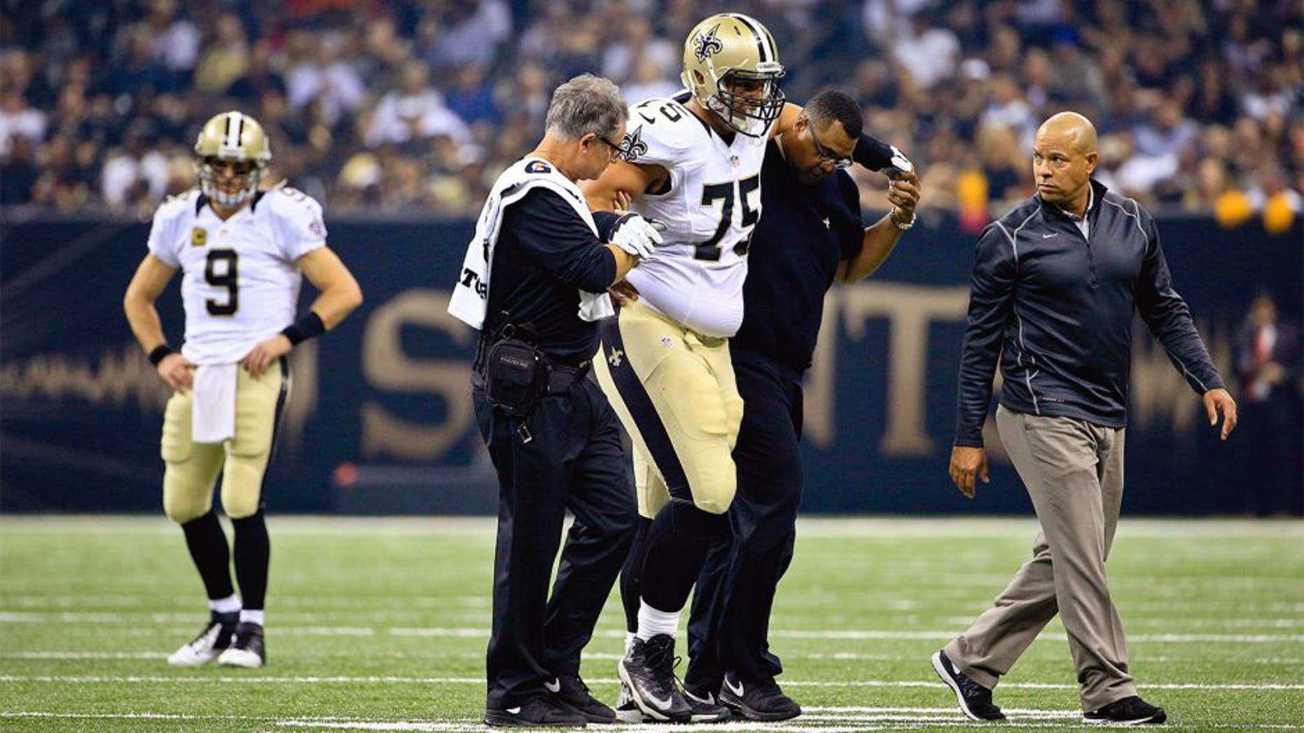 Oct 15, 2015; New Orleans, LA, USA; New Orleans Saints offensive tackle Andrus Peat (75) is helped off the field during the first quarter of a game against the Atlanta Falcons at the Mercedes-Benz Superdome. Mandatory Credit: Derick E. Hingle-USA TODAY Sports