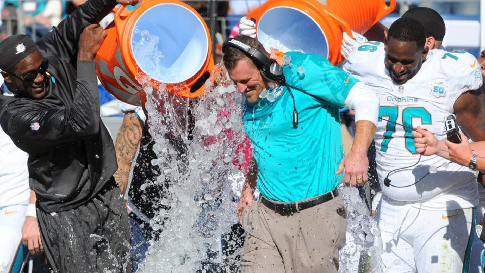 Oct 18, 2015; Nashville, TN, USA; Miami Dolphins interim head coach Dan Campbell is dumped with Gatorade after a win against the Tennessee Titans at Nissan Stadium. The Dolphins won 38-10. Mandatory Credit: Christopher Hanewinckel-USA TODAY Sports