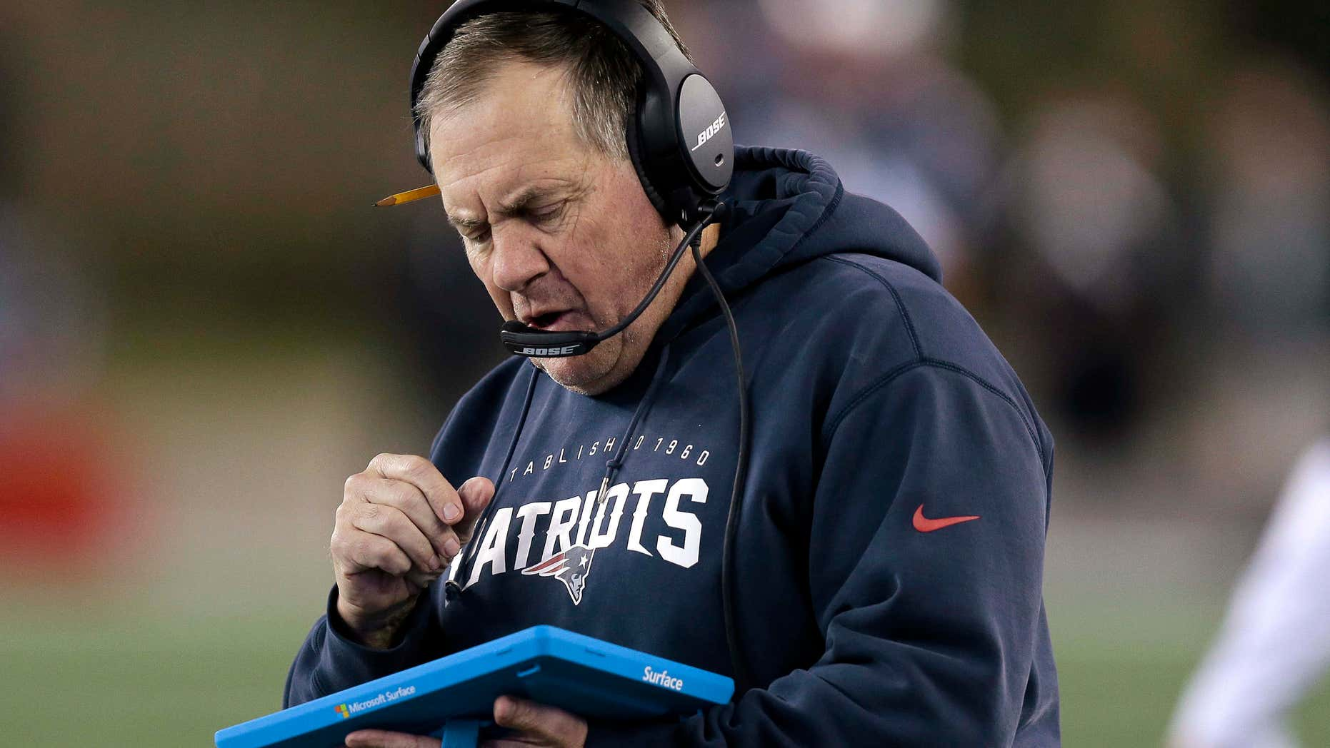 FILE - In this Dec. 6, 2015, file photo, New England Patriots head coach Bill Belichick studies a tablet device along the sideline during the first half of an NFL football game against the Philadelphia Eagles in Foxborough, Mass.