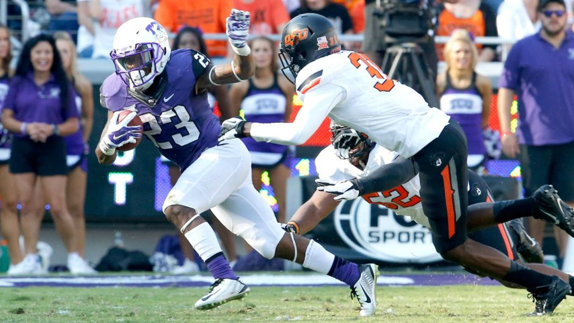 Oct 18, 2014; Fort Worth, TX, USA; TCU Horned Frogs tailback B.J. Catalon (23) runs with the ball against Oklahoma State Cowboys safety Tre Flowers (31) at Amon G. Carter Stadium. Mandatory Credit: Matthew Emmons-USA TODAY Sports