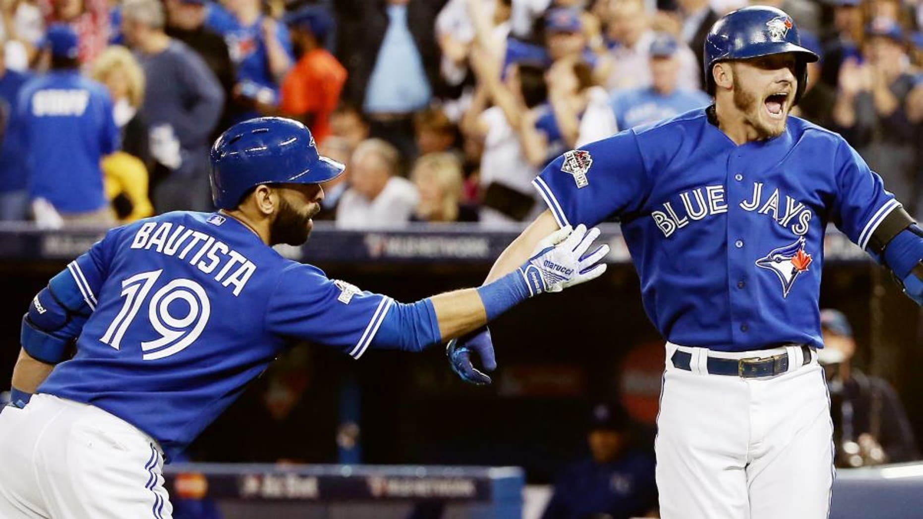 TORONTO, ON - OCTOBER 19: Josh Donaldson #20 of the Toronto Blue Jays celebrates with Jose Bautista #19 of the Toronto Blue Jays after hitting a two-run home run in the third inning against the Kansas City Royals during game three of the American League Championship Series at Rogers Centre on October 19, 2015 in Toronto, Canada. (Photo by Tom Szczerbowski/Getty Images)