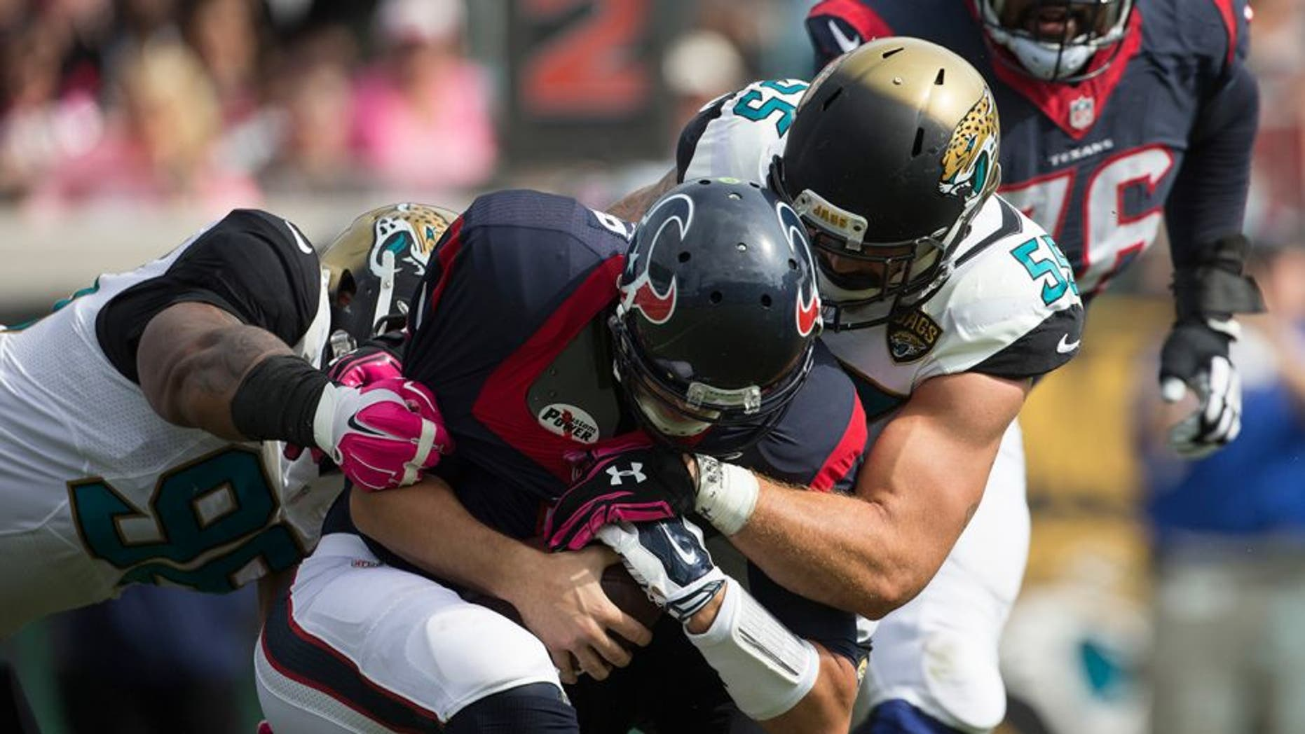 Oct 18, 2015; Jacksonville, FL, USA; Jacksonville Jaguars defensive tackle Roy Miller (97) and Jacksonville Jaguars outside linebacker Dan Skuta (55) sack Houston Texans quarterback Brian Hoyer (7) during the third quarter at EverBank Field. The Houston Texans won 31-20. Mandatory Credit: Logan Bowles-USA TODAY Sports