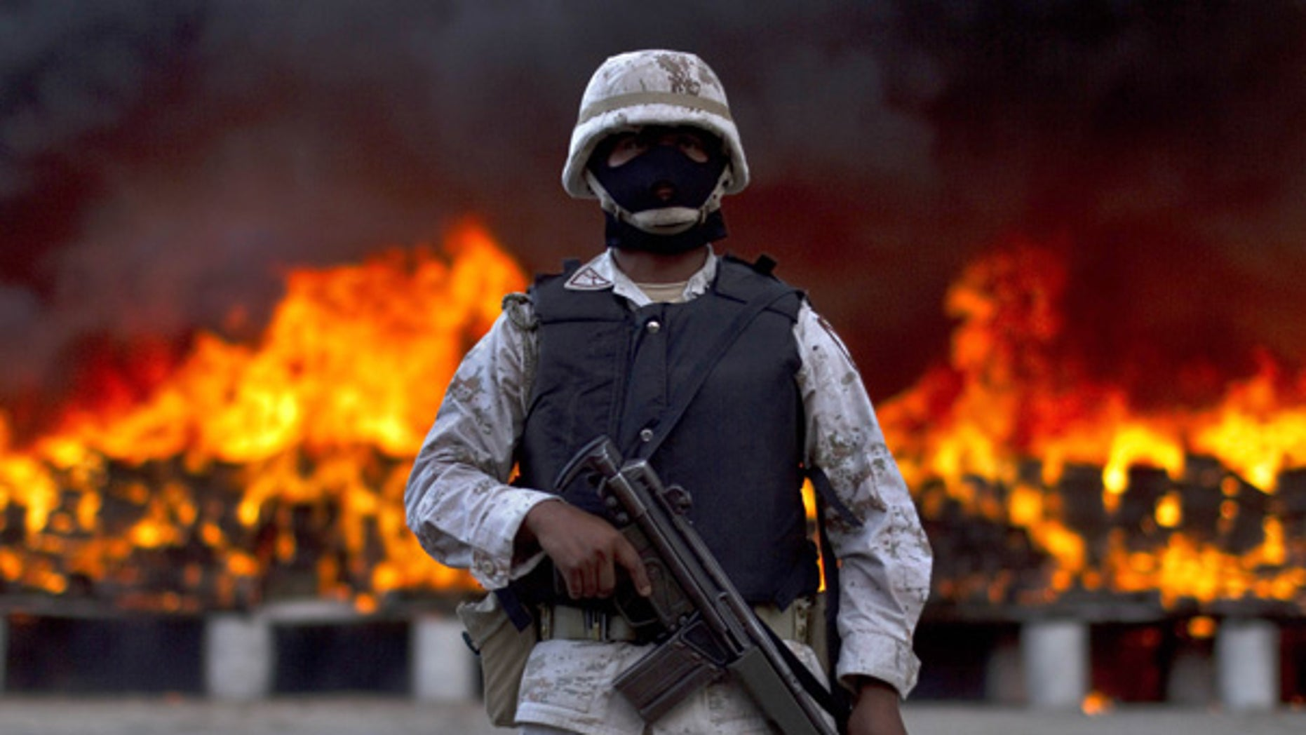 Oct. 20: A soldier guards packages of marijuana being incinerated after army and police seized 134 tons of U.S.-bound pot in Tijuana.