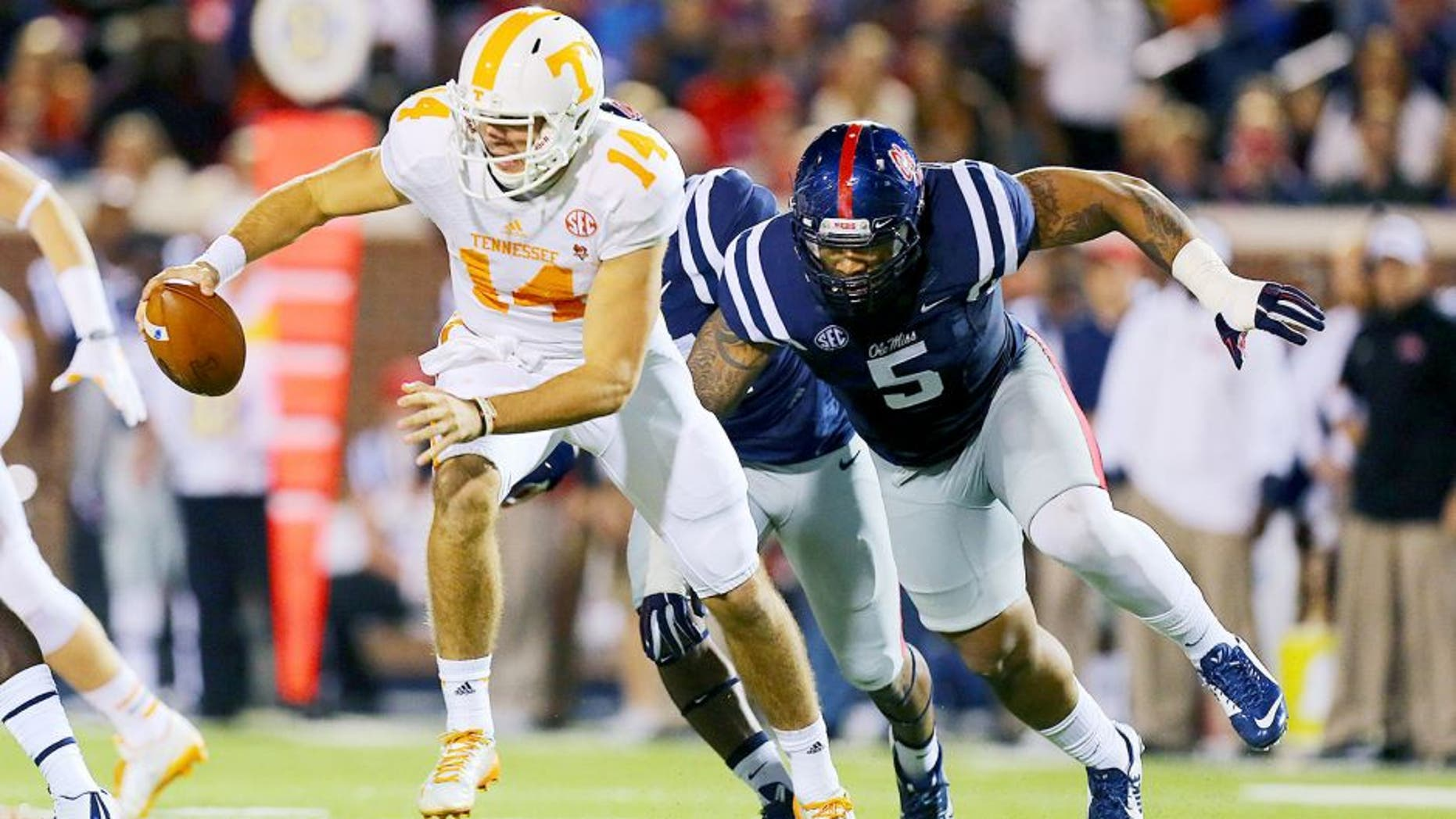 Oct 18, 2014; Oxford, MS, USA; Tennessee Volunteers quarterback Justin Worley (14) advances the ball while being chased by Mississippi Rebels defensive tackle Robert Nkemdiche (5) during the game at Vaught-Hemingway Stadium. Mandatory Credit: Spruce Derden-USA TODAY Sports