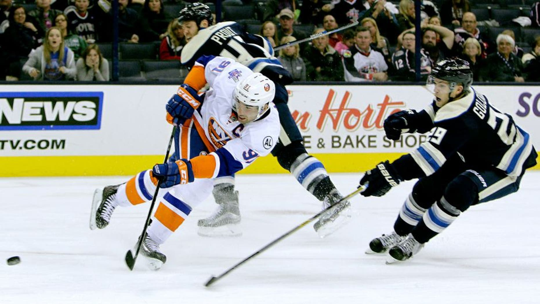 New York Islanders' John Tavares, left, shoots and scores a goal between Columbus Blue Jackets' Dalton Prout, back, and Cody Goloubef during the third period of an NHL hockey game Tuesday, Oct. 20, 2015, in Columbus, Ohio. The Islanders beat the Blue Jackets 4-0. (AP Photo/Jay LaPrete)