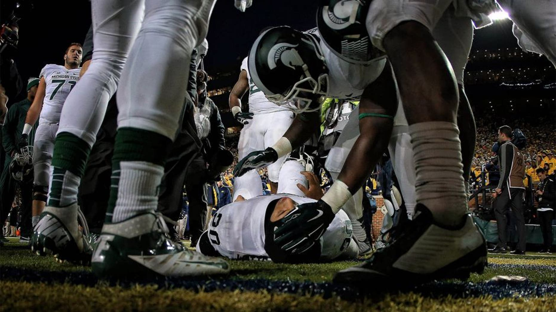 Oct 17, 2015; Ann Arbor, MI, USA; Injured Michigan State Spartans defensive back Jalen Watts-Jackson (20) is talked to by teamates before being carted off the field during the 2nd half of a game at Michigan Stadium. Mandatory Credit: Mike Carter-USA TODAY Sports