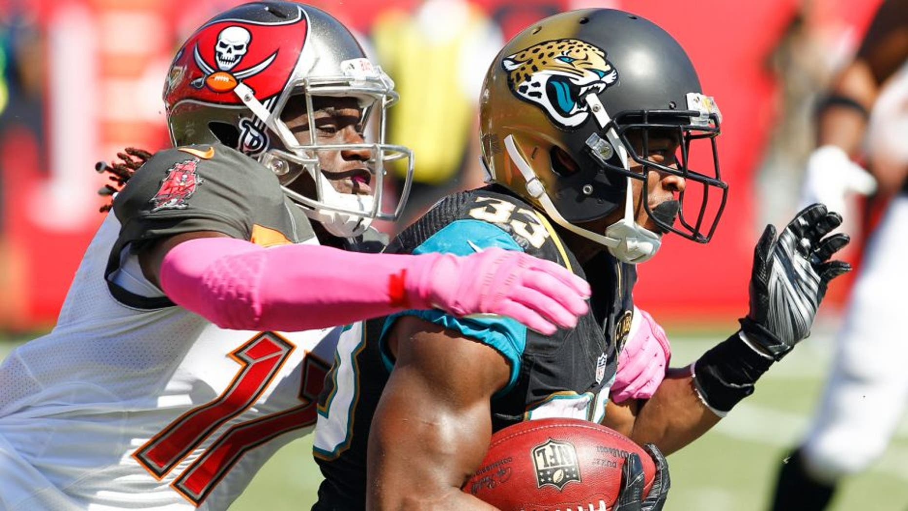 Oct 11, 2015; Tampa, FL, USA; Jacksonville Jaguars running back Corey Grant (33) is tackled from behind by Tampa Bay Buccaneers wide receiver Donteea Dye (17) during the second half of an NFL football game at Raymond James Stadium. Tampa won 38-31. Mandatory Credit: Reinhold Matay-USA TODAY Sports