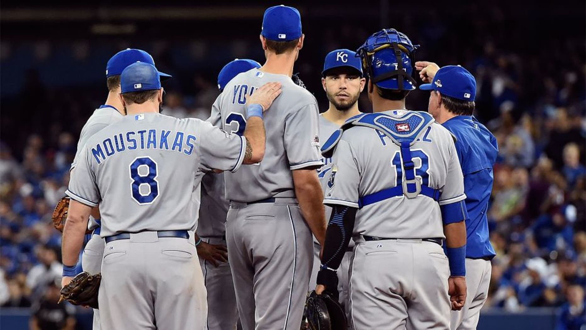Oct 20, 2015; Toronto, Ontario, CAN; Kansas City Royals starting pitcher Chris Young (32) is patted on the back by third baseman Mike Moustakas (8) as manager Ned Yost (3) relieves him during the fifth inning against the Toronto Blue Jays in game four of the ALCS at Rogers Centre. Mandatory Credit: Dan Hamilton-USA TODAY Sports