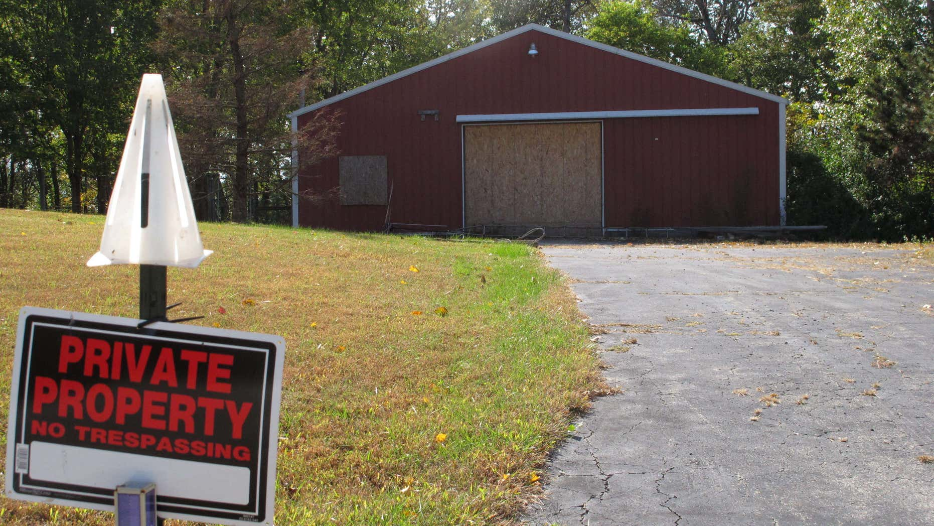 In this Tuesday, Oct. 18, 2016 photo, a private property sign guards the boarded up garage on property on Union Hill Road near the trailer where the bodies of Dana Rhoden and her children, Chris Rhoden Jr., and Hanna Rhoden, were found on April 22, three of eight family members found shot to death that day in a still-unsolved crime, in Piketon, Ohio.