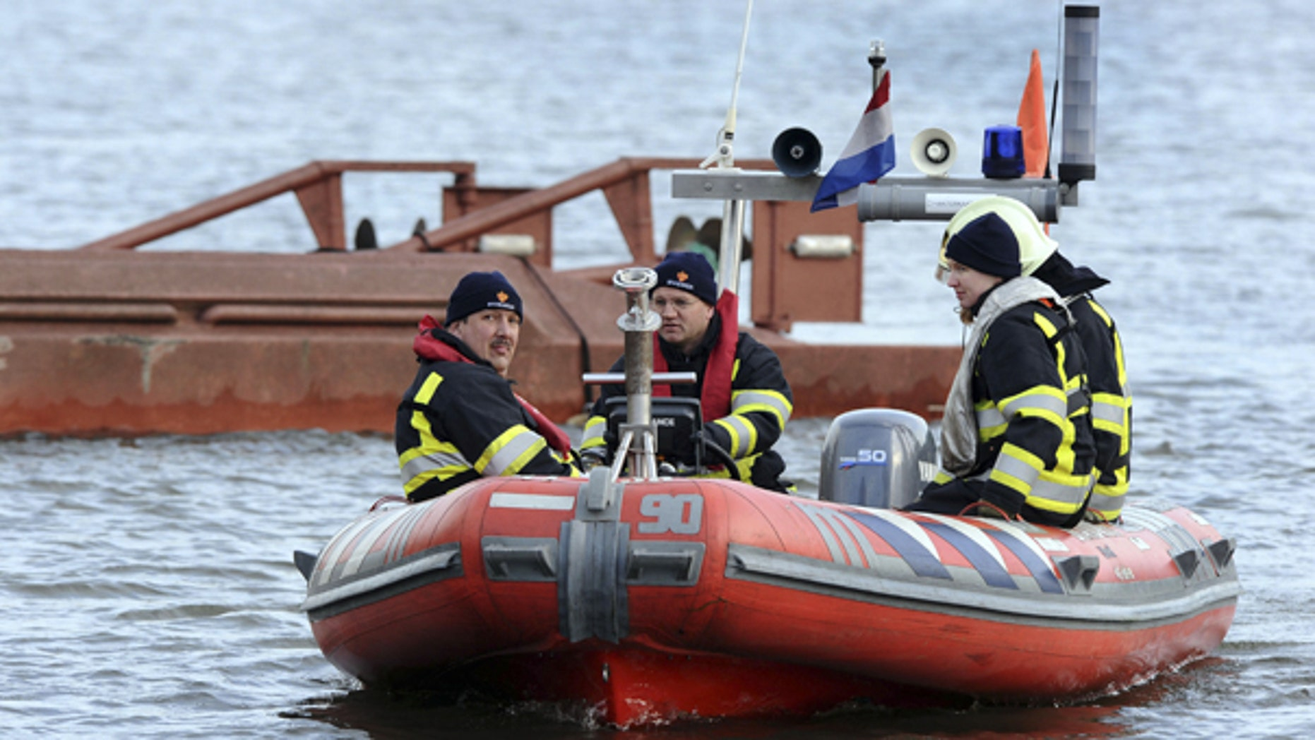 Oct. 22: Rescue workers are seen near a capsized ferry, rear, after a German freight ship struck a small Dutch passenger ferry in a canal near Amsterdam.