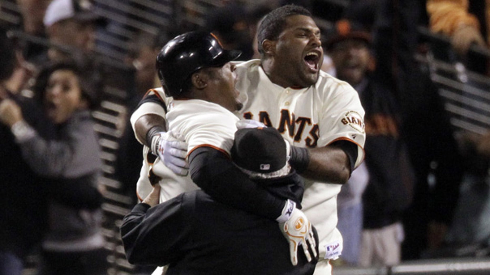 Oct. 20: San Francisco Giants' Juan Uribe, left, celebrates with Pablo Sandoval, right, after hitting a game-winning sacrifice fly during the ninth inning.