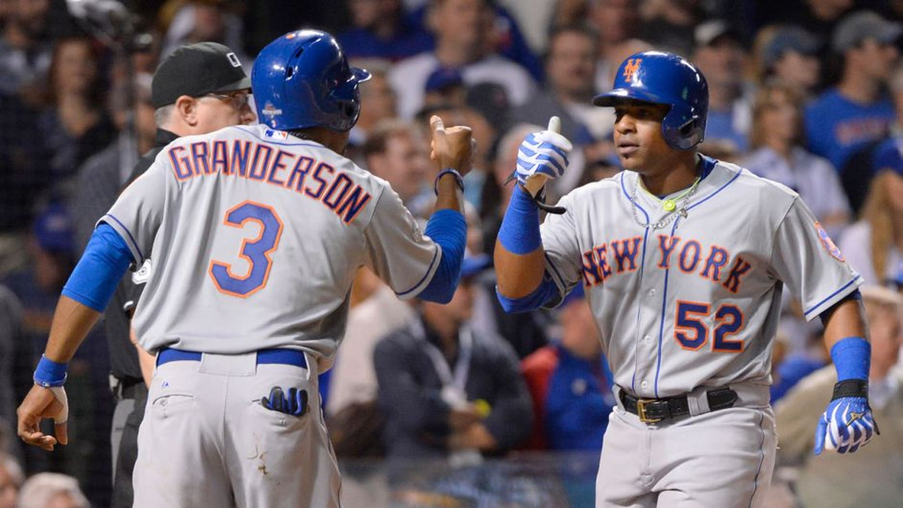 CHICAGO, IL - OCTOBER 21: Curtis Granderson #3 of the New York Mets and teammate Yoenis Cespedes #52 score on Lucas Duda's three-run home run in the top of the first inning of Game 4 of the NLCS against the Chicago Cubs at Wrigley Field on Wednesday, October 21, 2015 in Chicago, Illinois. (Photo by Ron Vesely/MLB Photos via Getty Images)
