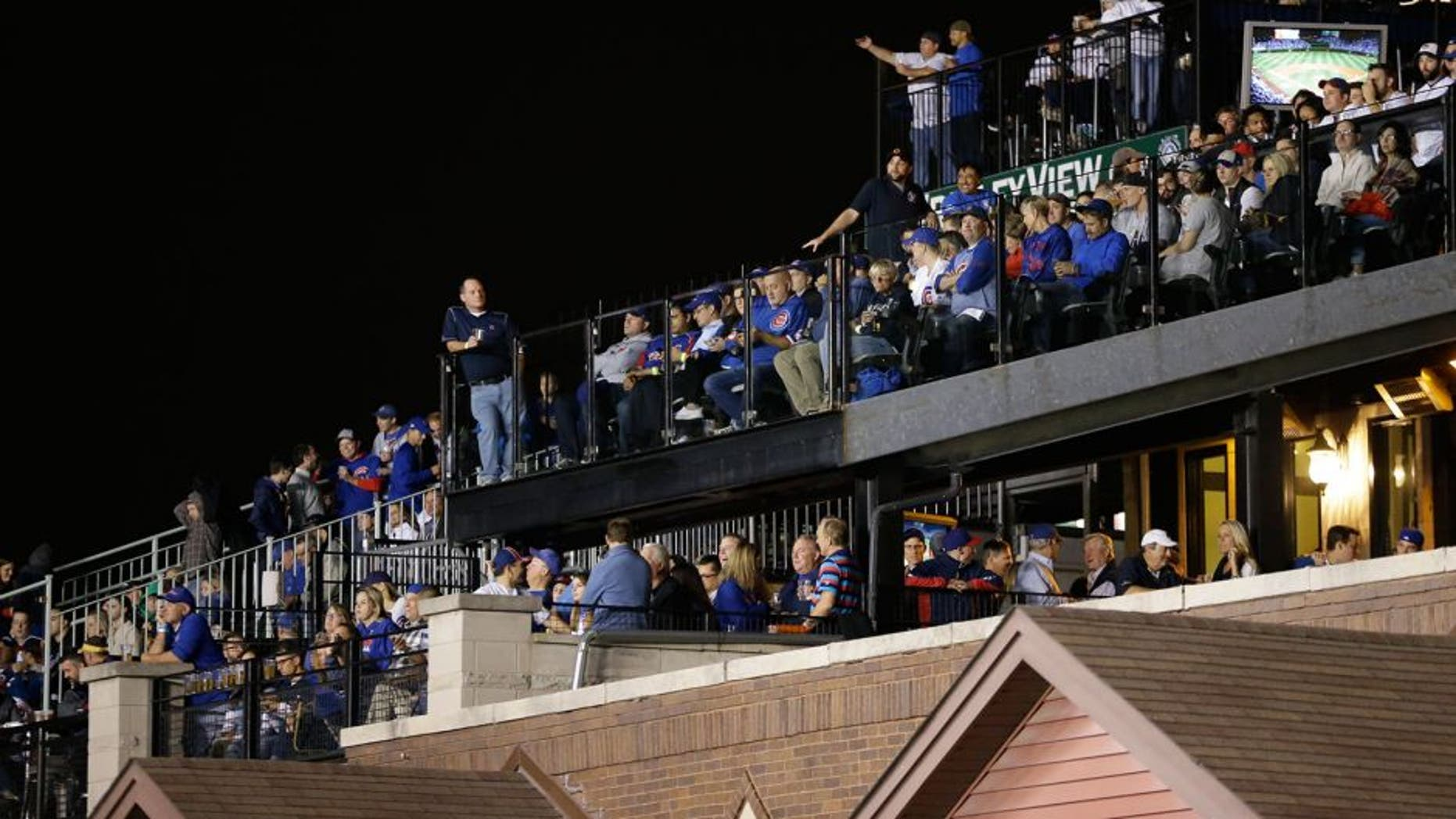 In this Oct. 20, 2015 photo, fans watch Game 3 of the National League baseball championship series between the Chicago Cubs and the New York Mets in Chicago, from the rooftop deck across the street beyond Wrigley Field's ivy-covered wall. With the massive Jumbotron now standing between the rooftop bleachers and the field, the 2015 postseason is the first for the Cubs since the team sliced into the views from the rooftops - one of the fabled experiences at this venerable old ballpark, and one in serious danger of going away for good. (AP Photo/David Goldman)
