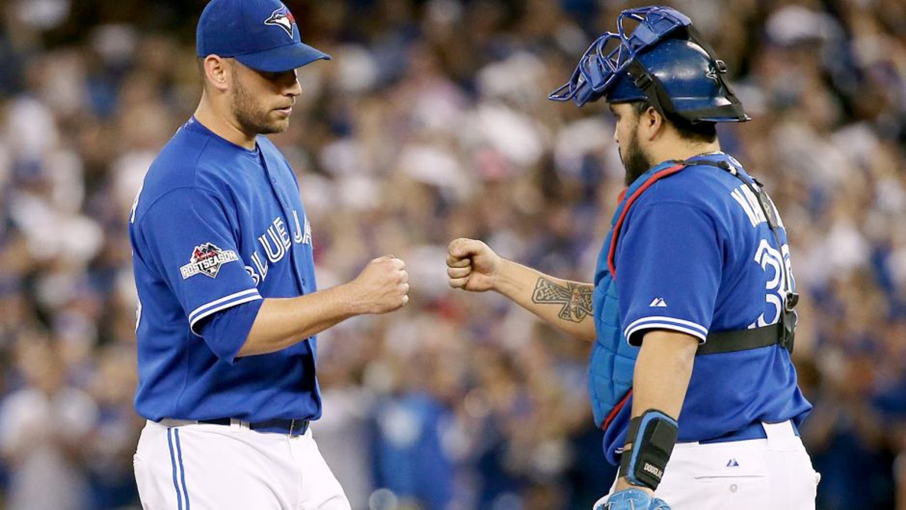 TORONTO, ON - OCTOBER 21: Toronto Blue Jays starting pitcher Marco Estrada (25) (left) gets a fist bump from catcher Dioner Navarro just before he's pulled from the game in the 7th inning. Toronto Blue Jays V Kansas City Royals in Game 5 of the American League Championship Series in MLB action at Rogers Centre. Jays win 7-1 and head back to KC for Game 6 trailing in the series 3-2. Toronto Star/Rick Madonik (Rick Madonik/Toronto Star via Getty Images)