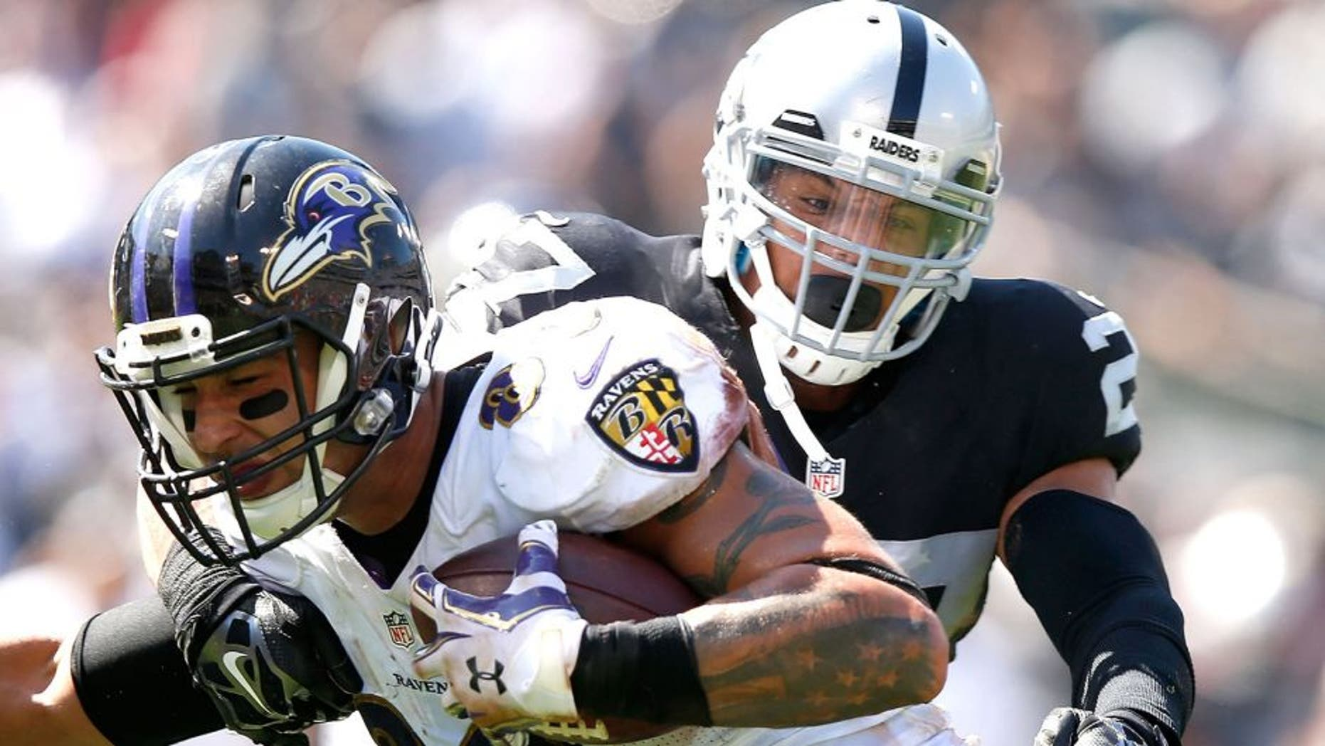 OAKLAND, CA - SEPTEMBER 20: Crockett Gillmore #80 of the Baltimore Ravens carries for a touchdown against the block of Taylor Mays #27 of the Oakland Raiders in the second quarter against the Oakland Raiders at Oakland-Alameda County Coliseum on September 20, 2015 in Oakland, California. (Photo by Ezra Shaw/Getty Images)