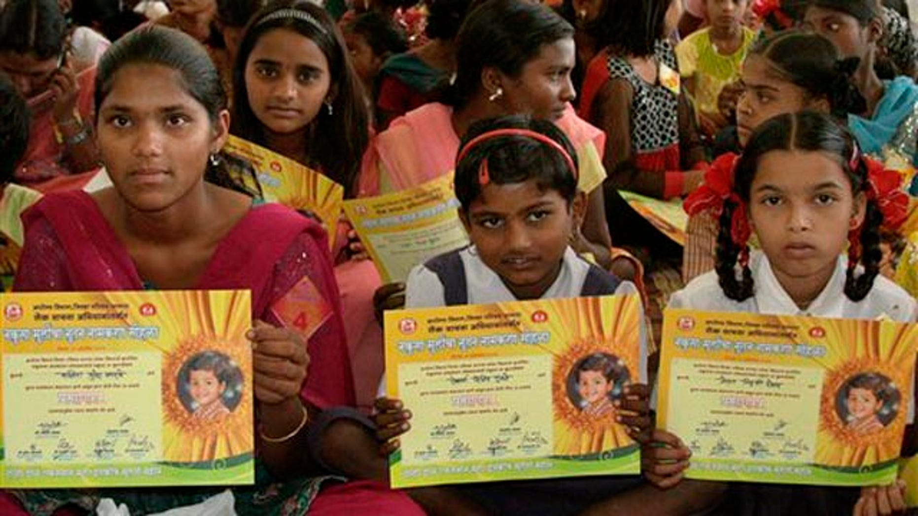 October 22, 2011: Girls hold certificates stating their new official names during a renaming ceremony  in Satara, India.