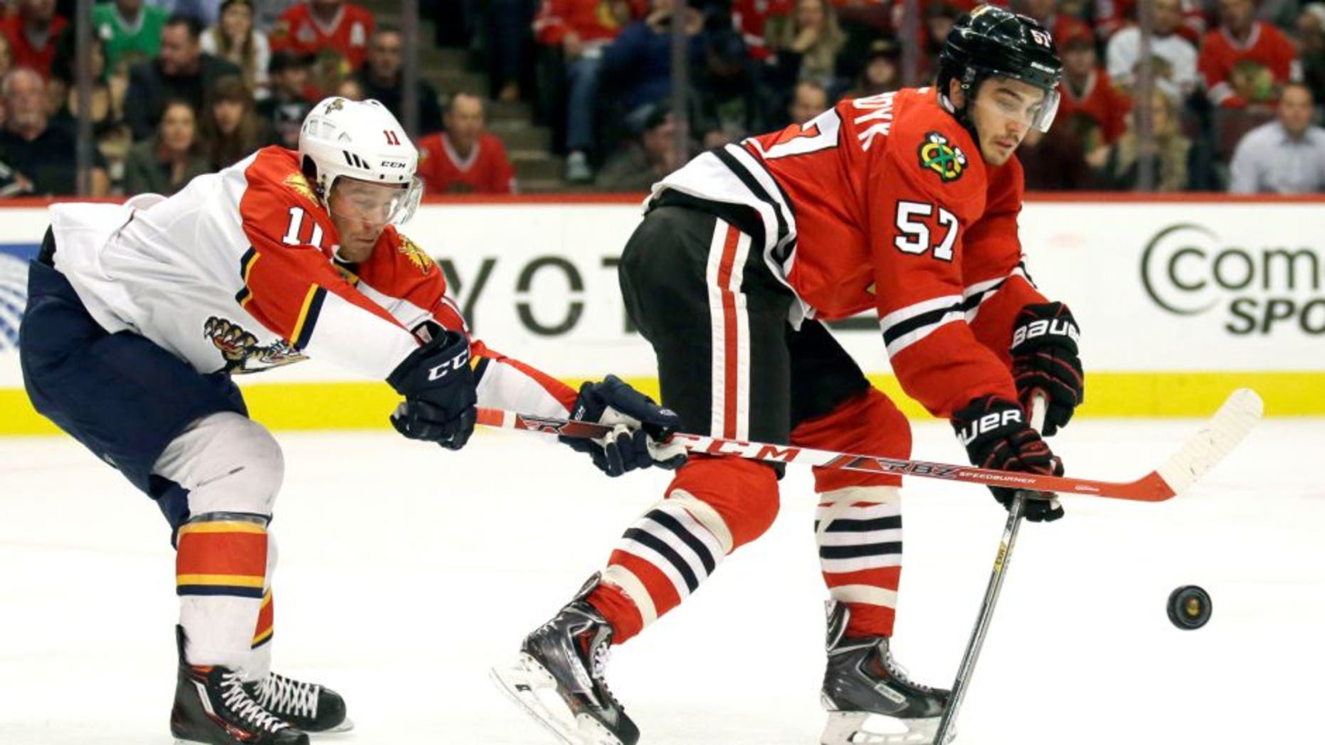 Florida Panthers left wing Jonathan Huberdeau, left, and Chicago Blackhawks defenseman Trevor van Riemsdyk battle for the puck during the first period of an NHL hockey game Thursday, Oct. 22, 2015, in Chicago. (AP Photo/Nam Y. Huh)