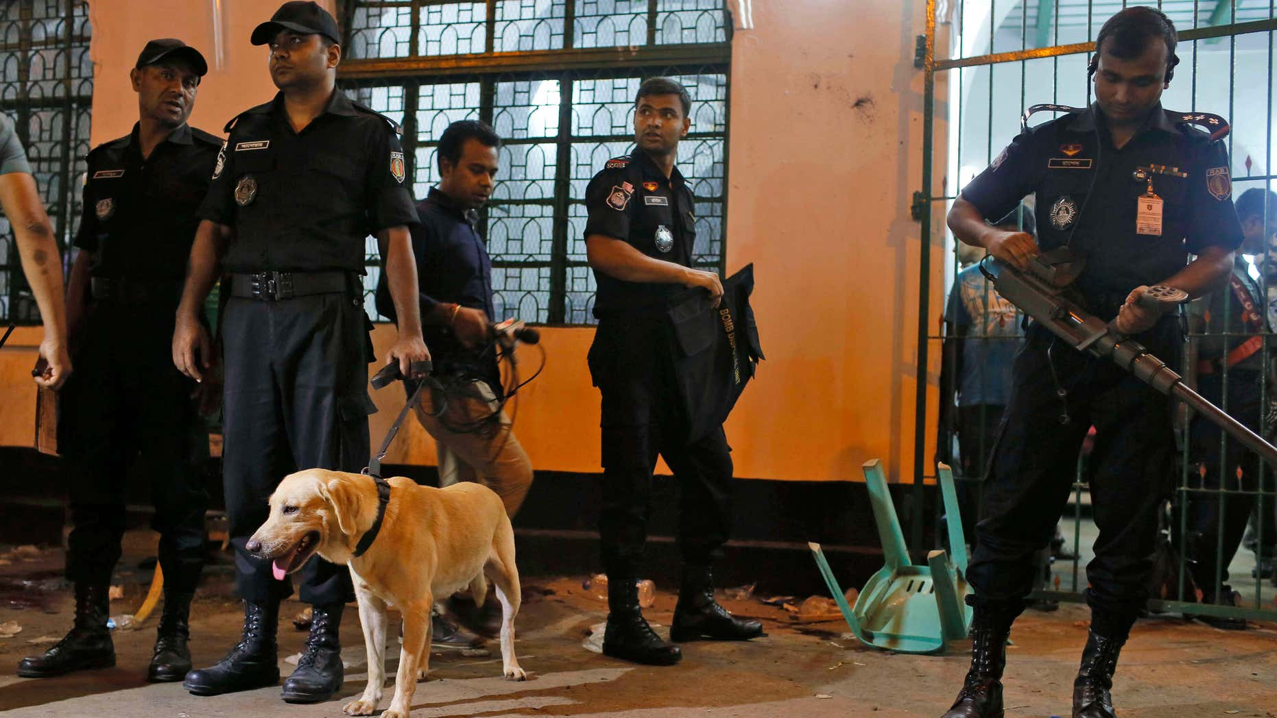 Oct. 24, 2015: Bangladeshi security personnel stand with a sniffer dog at the site of an explosion in Dhaka, Bangladesh.