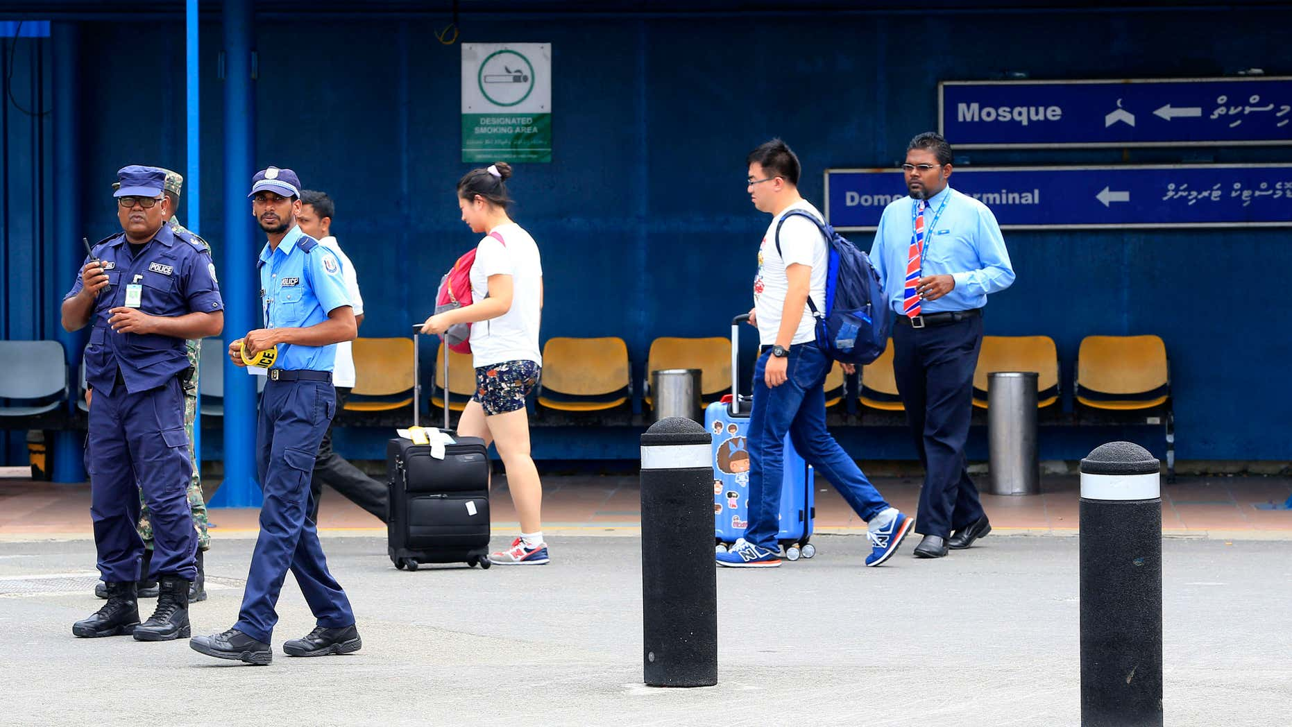 Oct. 24, 2015: Police prepare to cordon off an area before the arrival of Vice President Ahmed Adheeb at the International Airport in Male, Maldives.