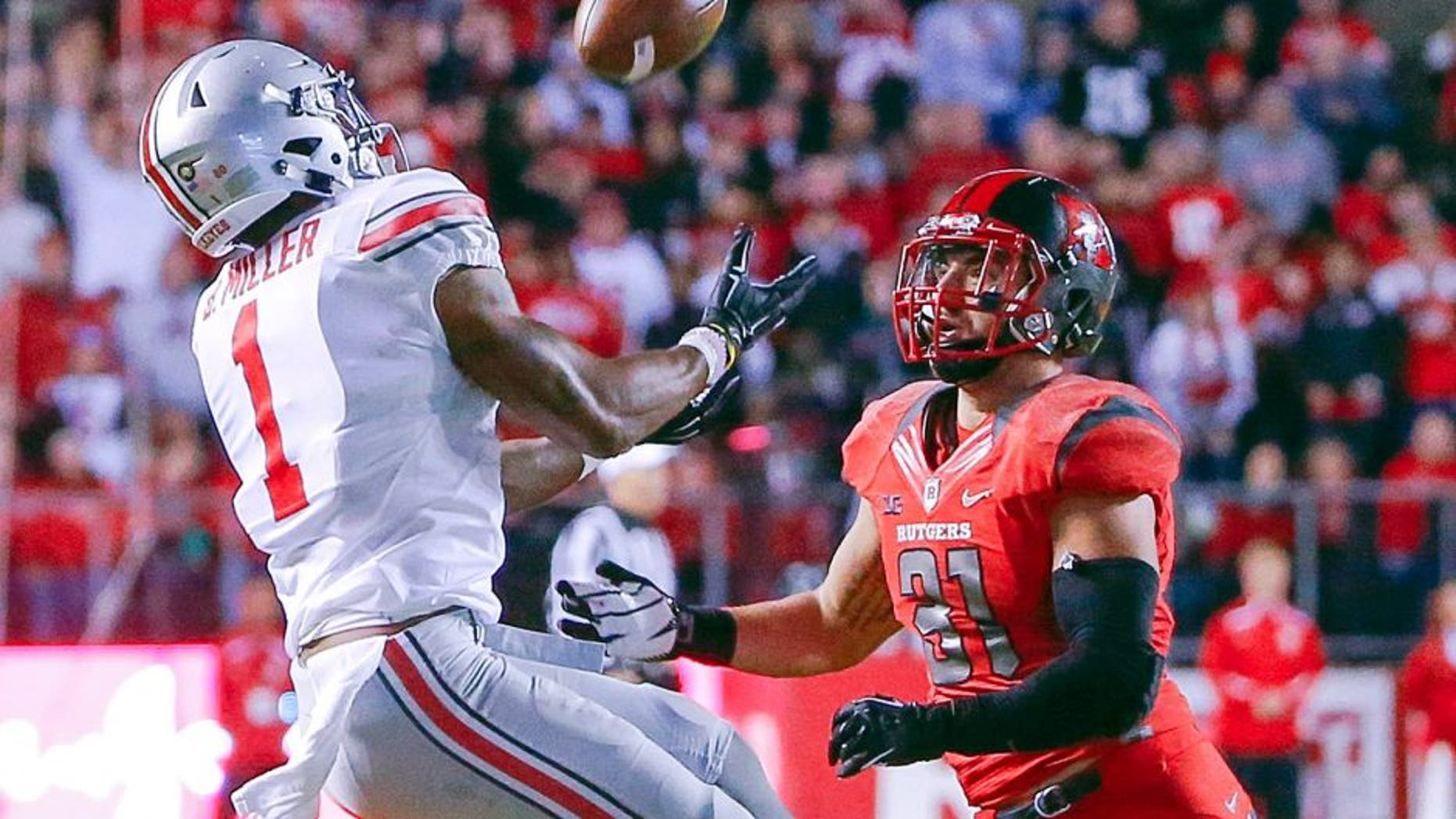 Oct 24, 2015; Piscataway, NJ, USA; Ohio State Buckeyes wide receiver Braxton Miller (1) pulls in long pass during the second quarter against Rutgers Scarlet Knights running back Charles Snorweah (21) at High Points Solutions Stadium. Mandatory Credit: Jim O'Connor-USA TODAY Sports