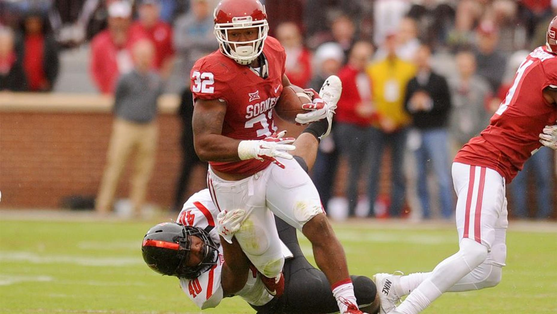 Oct 24, 2015; Norman, OK, USA; Oklahoma Sooners running back Samaje Perine (32) runs through a tackle attempt by Texas Tech Red Raiders linebacker Dakota Allen (40) during the second quarter at Gaylord Family - Oklahoma Memorial Stadium. Mandatory Credit: Mark D. Smith-USA TODAY Sports